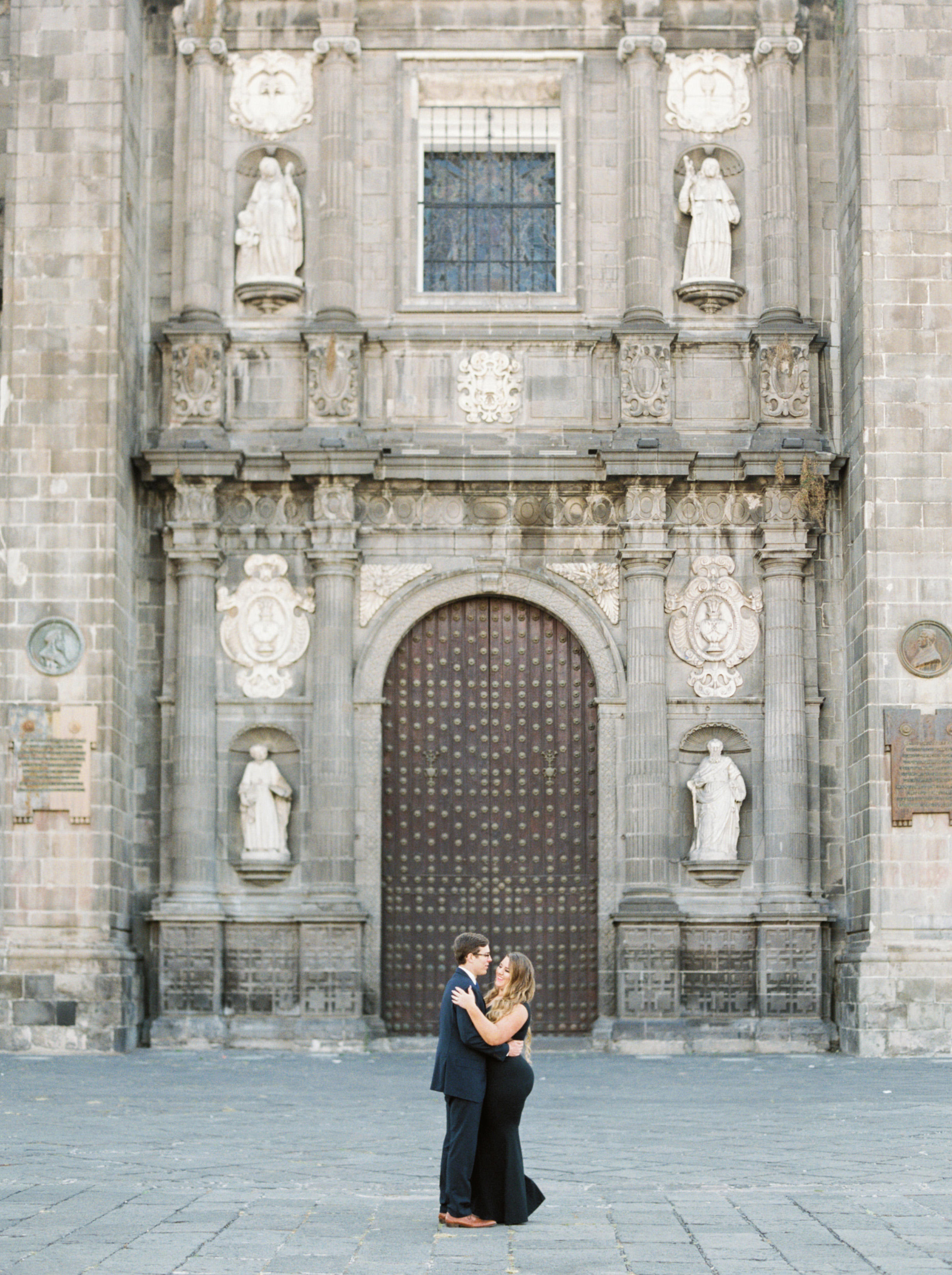 destination engagement couple pose in front of architectural building