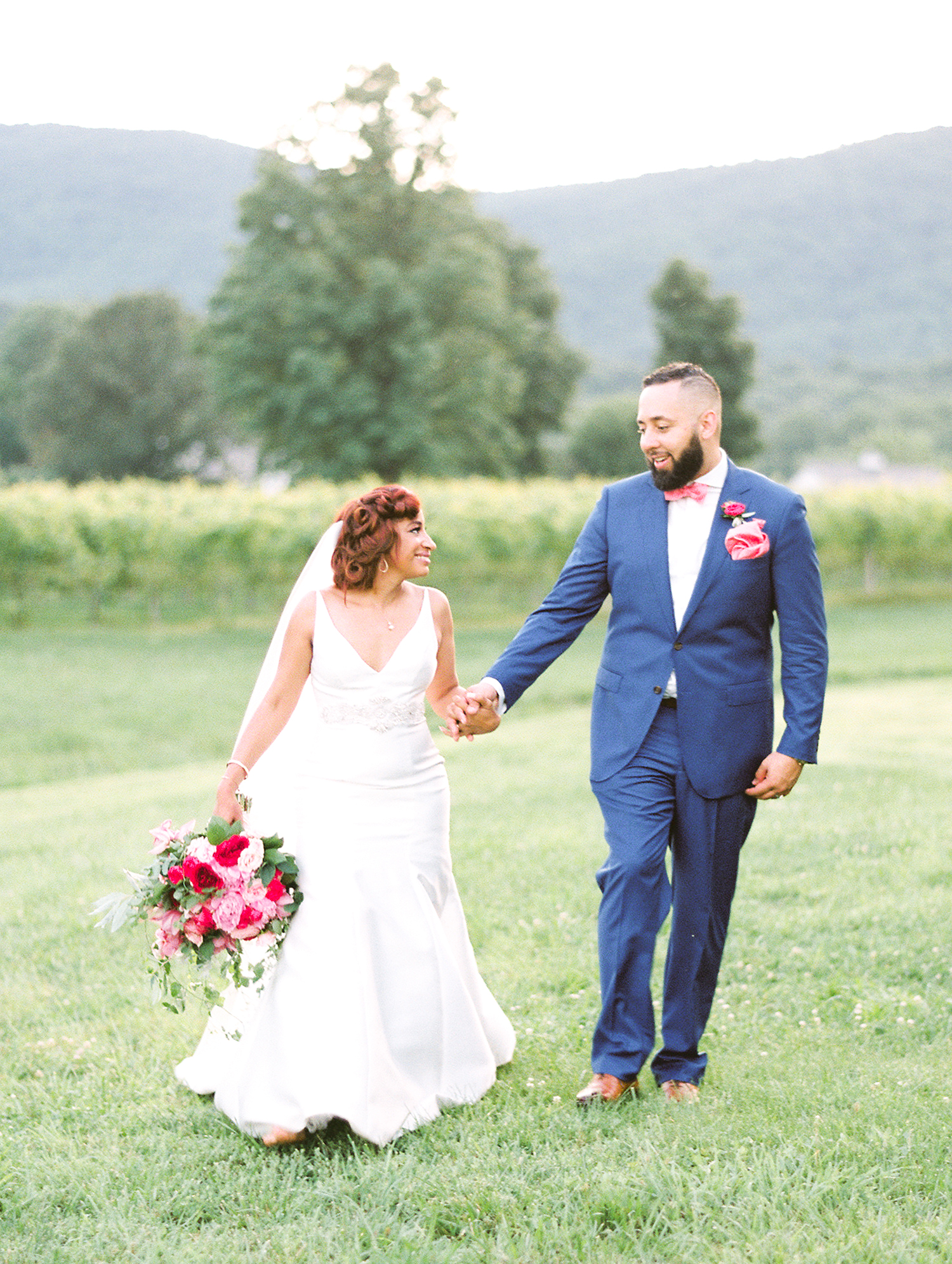 dawn rich wedding couple holding hands in field