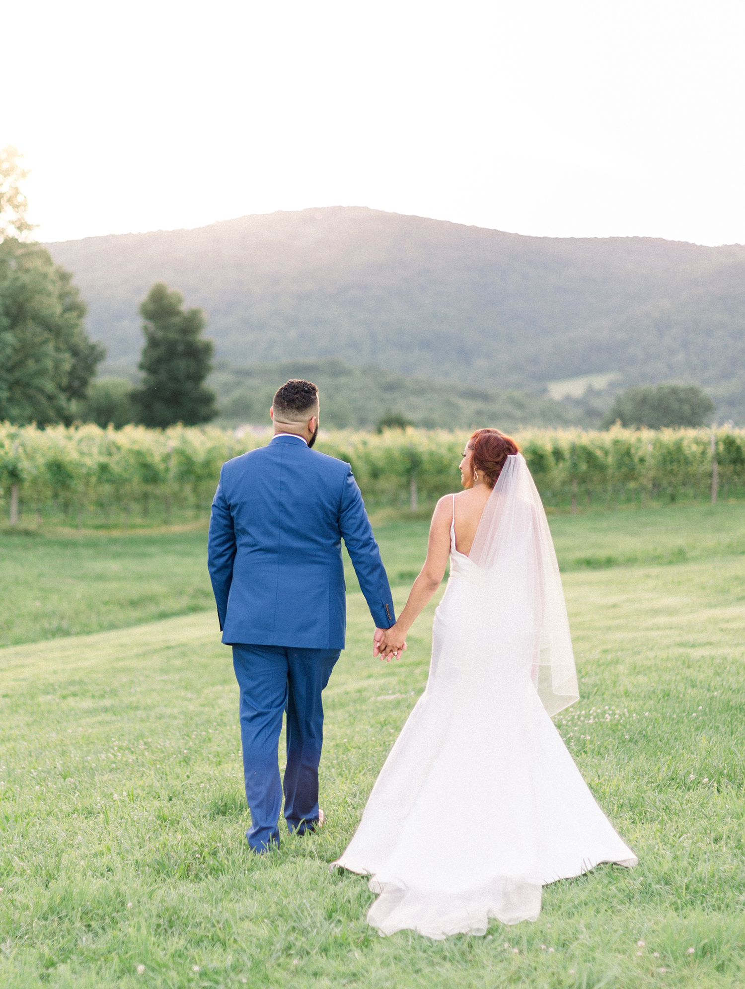 dawn rich wedding couple holding hands in field with mountain behind