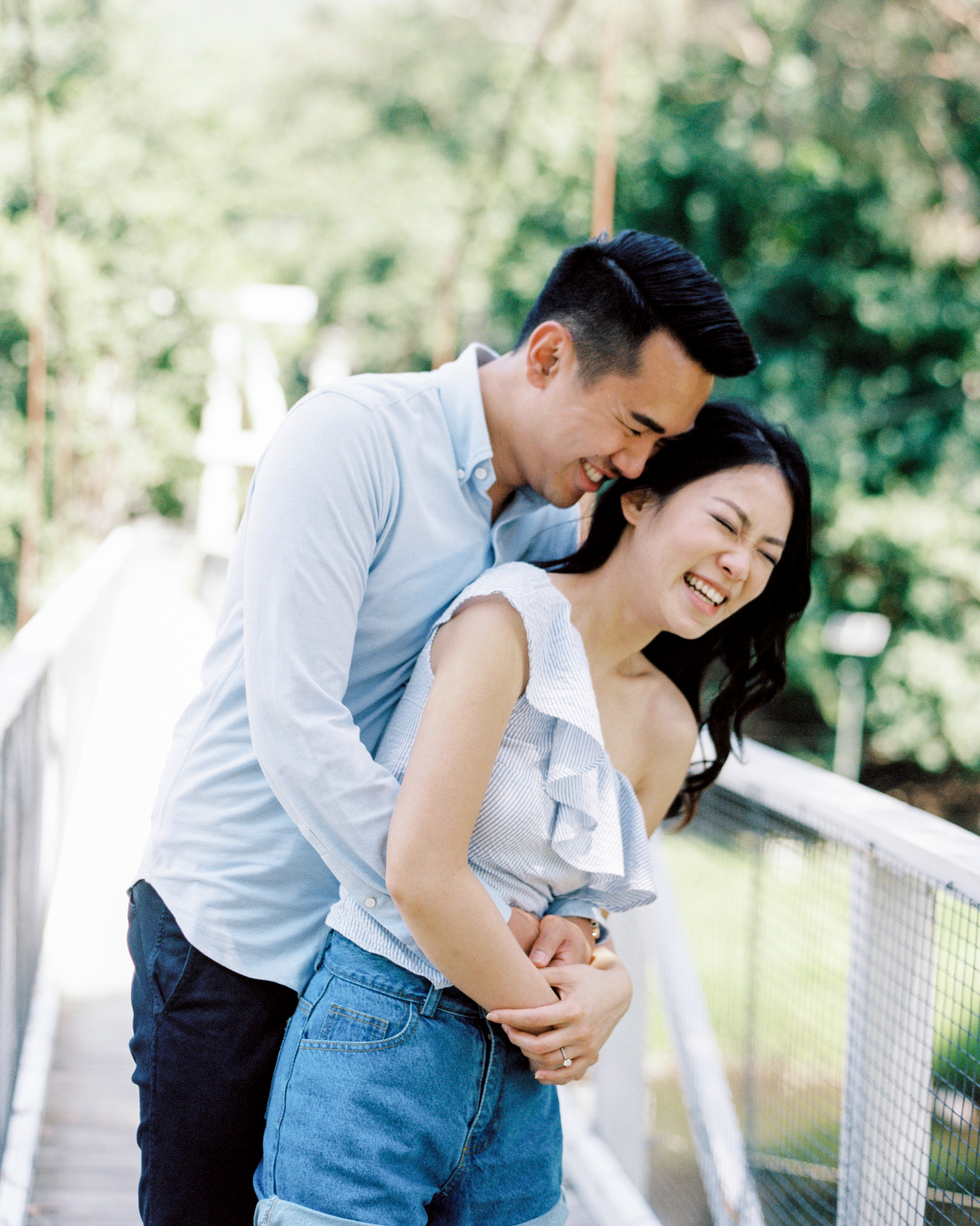 couple laughing on bridge engagement photo