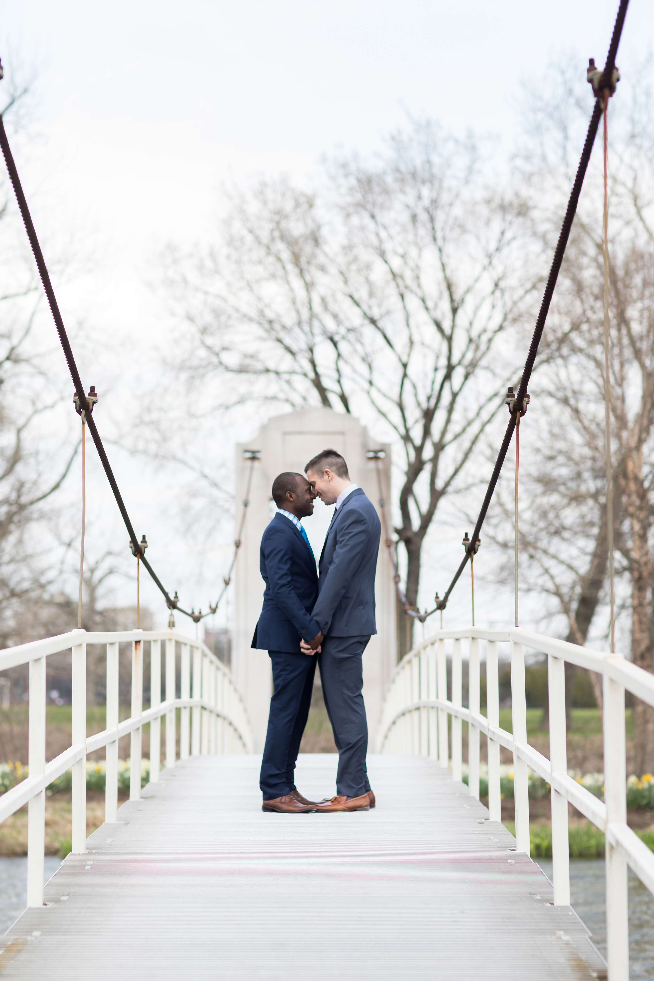 couple embrace on bridge engagement
