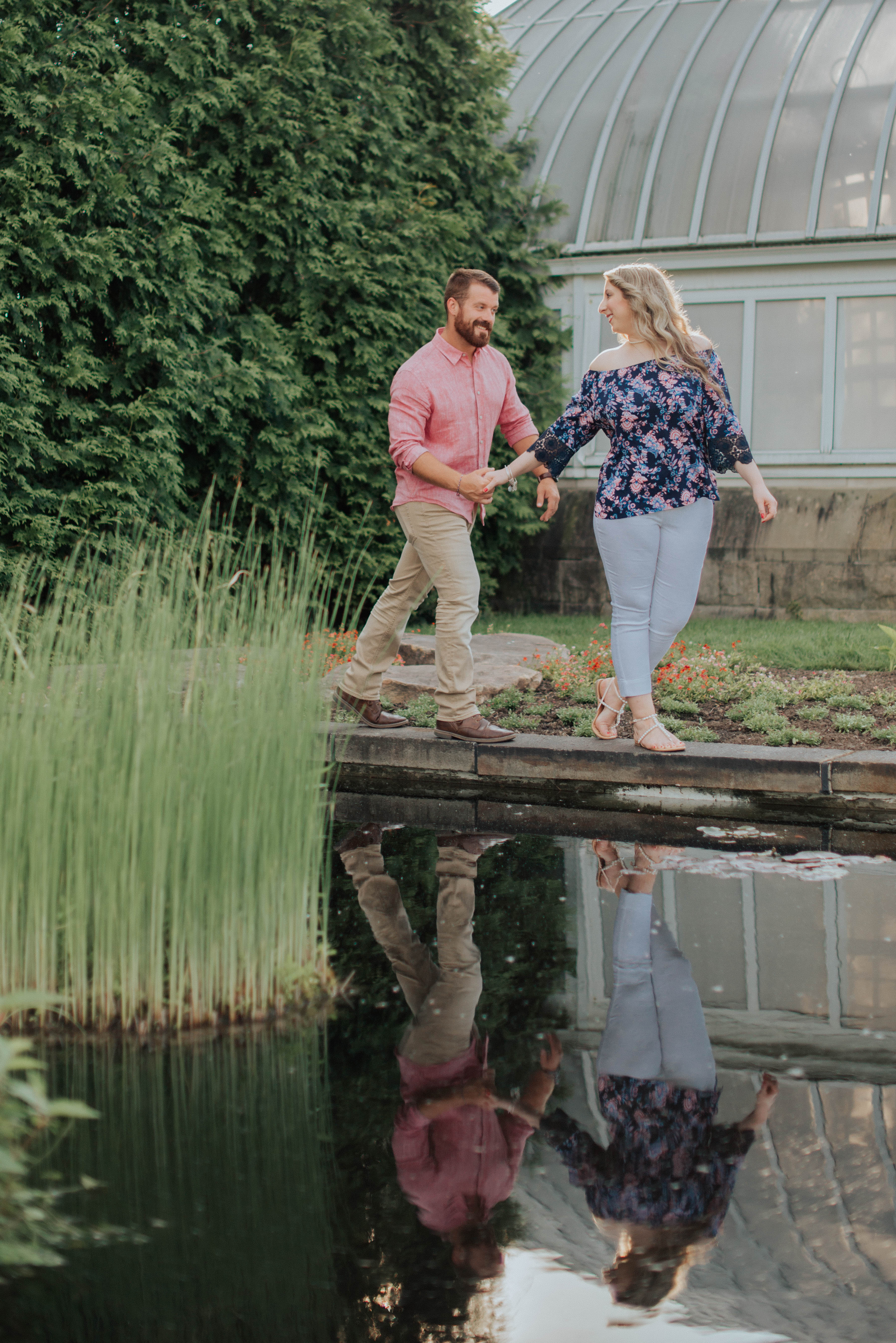 engagement photo couple walking by pond