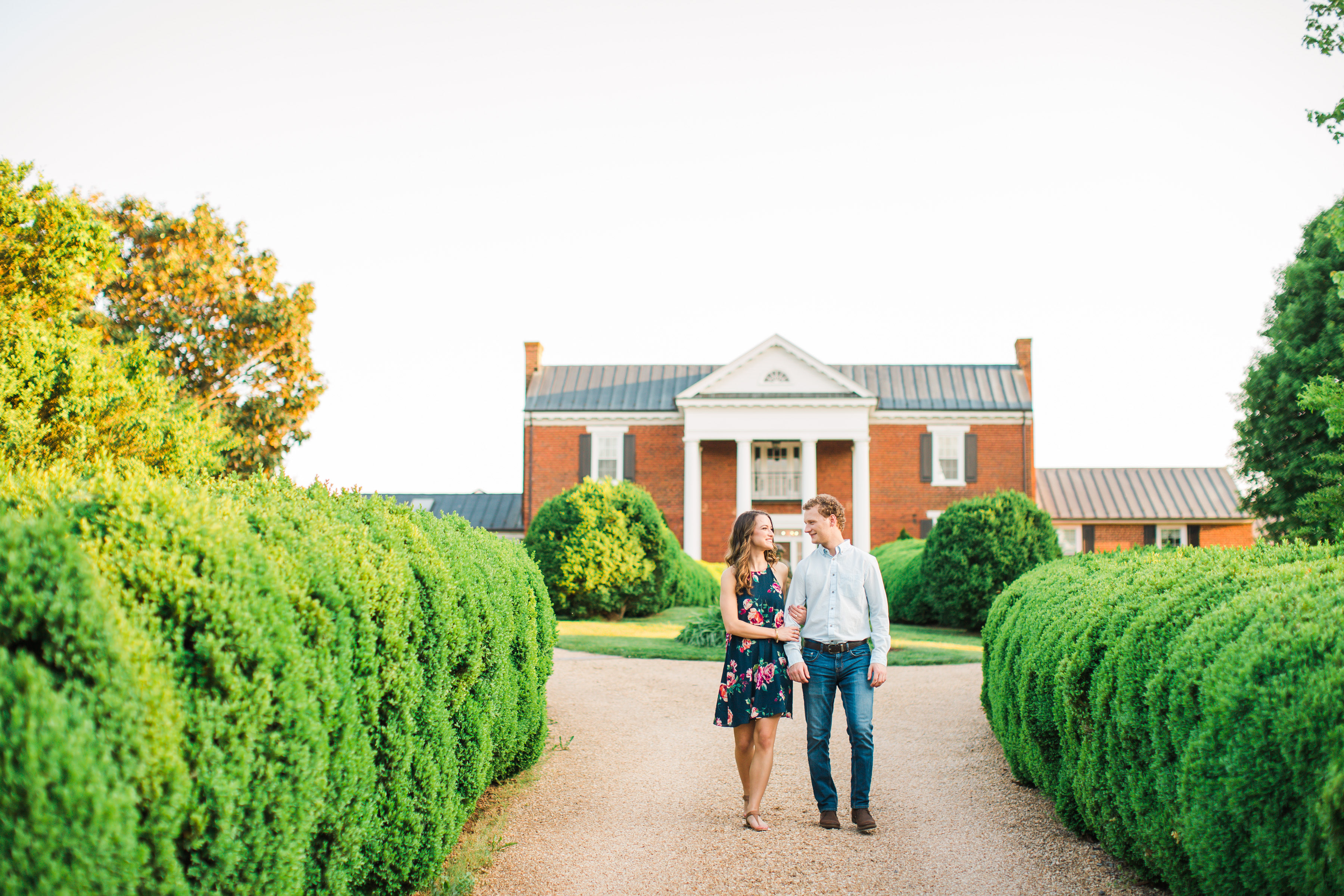 couple walking on estate engagement photo