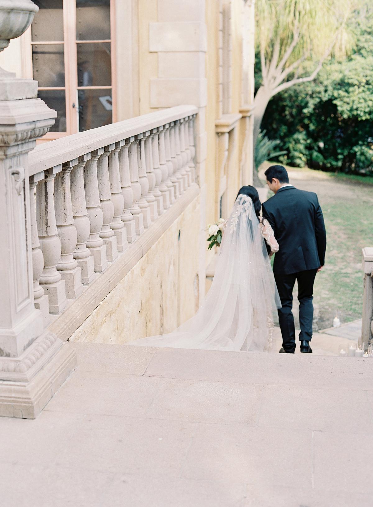emme daji wedding back of couple walking down stairs
