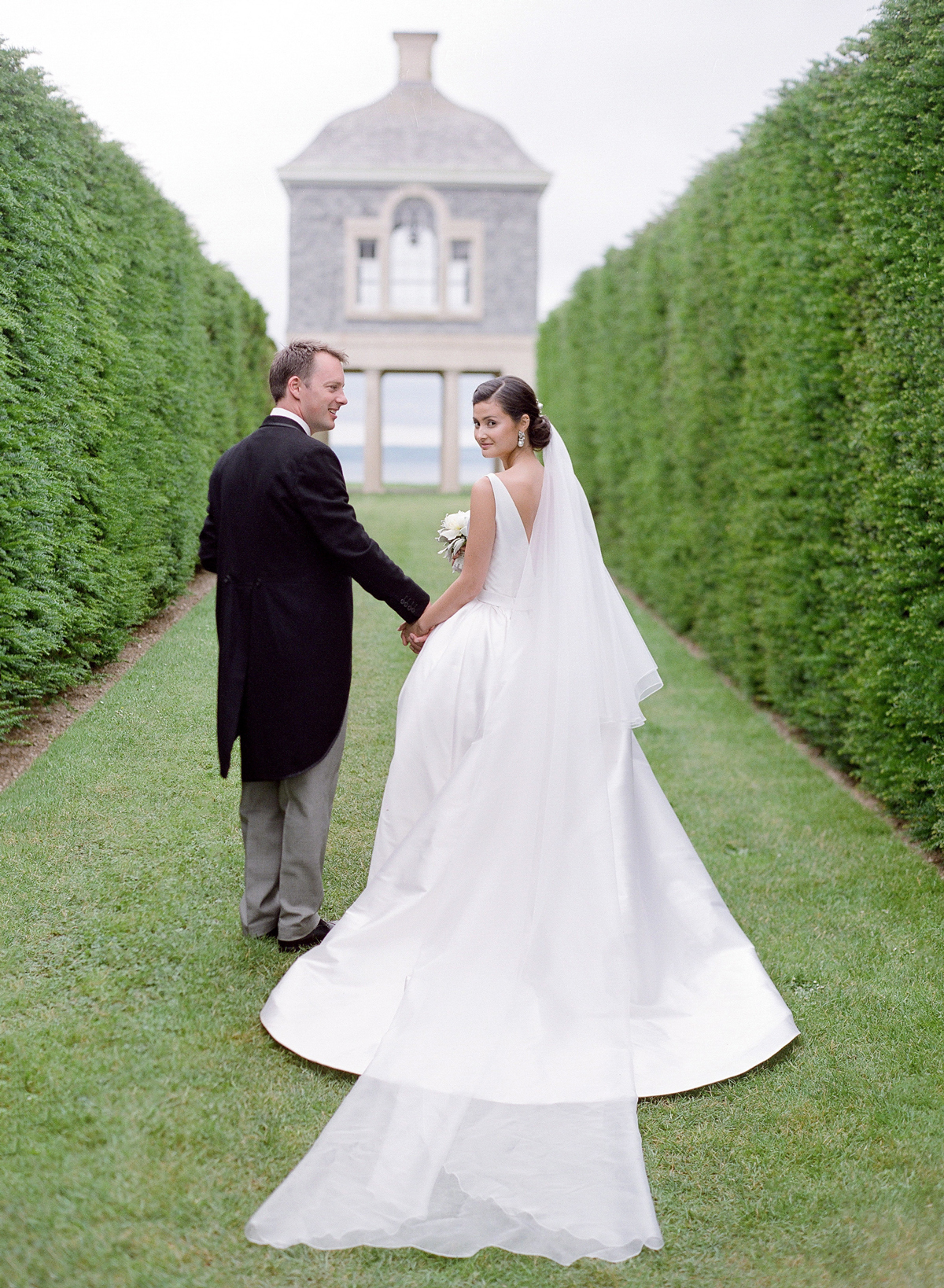 peony matthew england wedding couple holding hands bride looking back