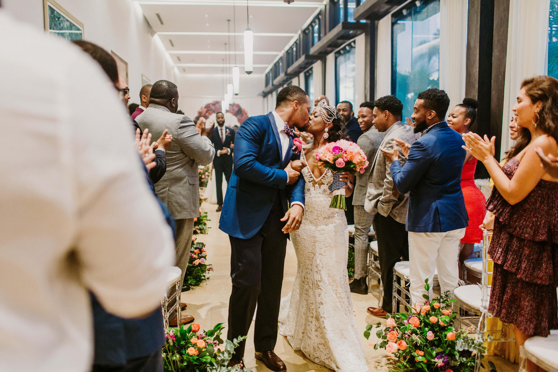 bride groom kiss aisle guests applaud