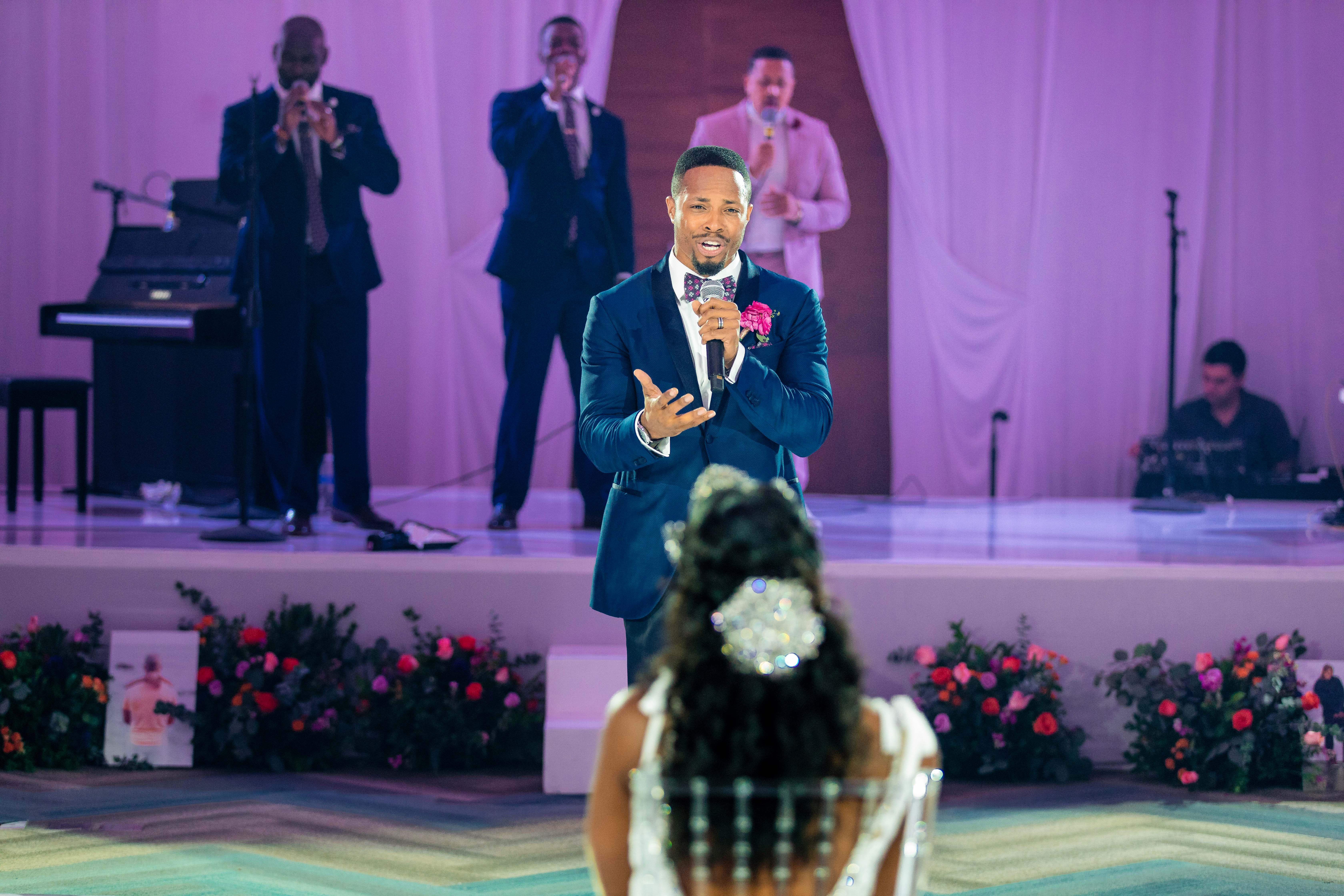 wedding reception groom sings to bride