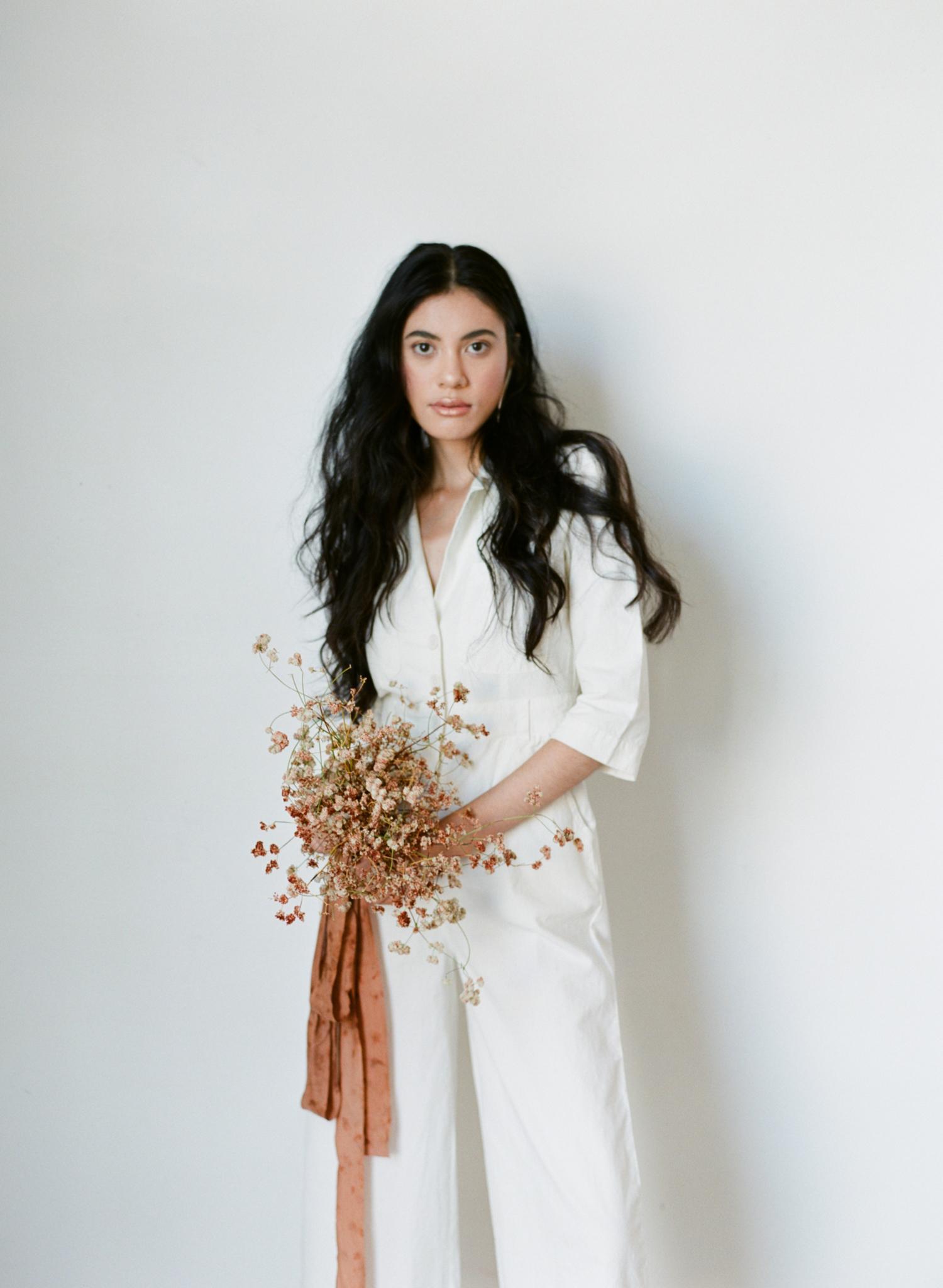 single flower wedding bouquet dried wildflowers held by bride in jumpsuit