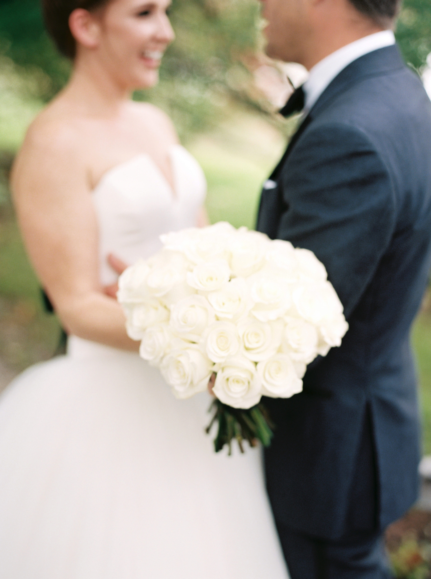 single flower wedding bouquet white roses held by bride embracing groom