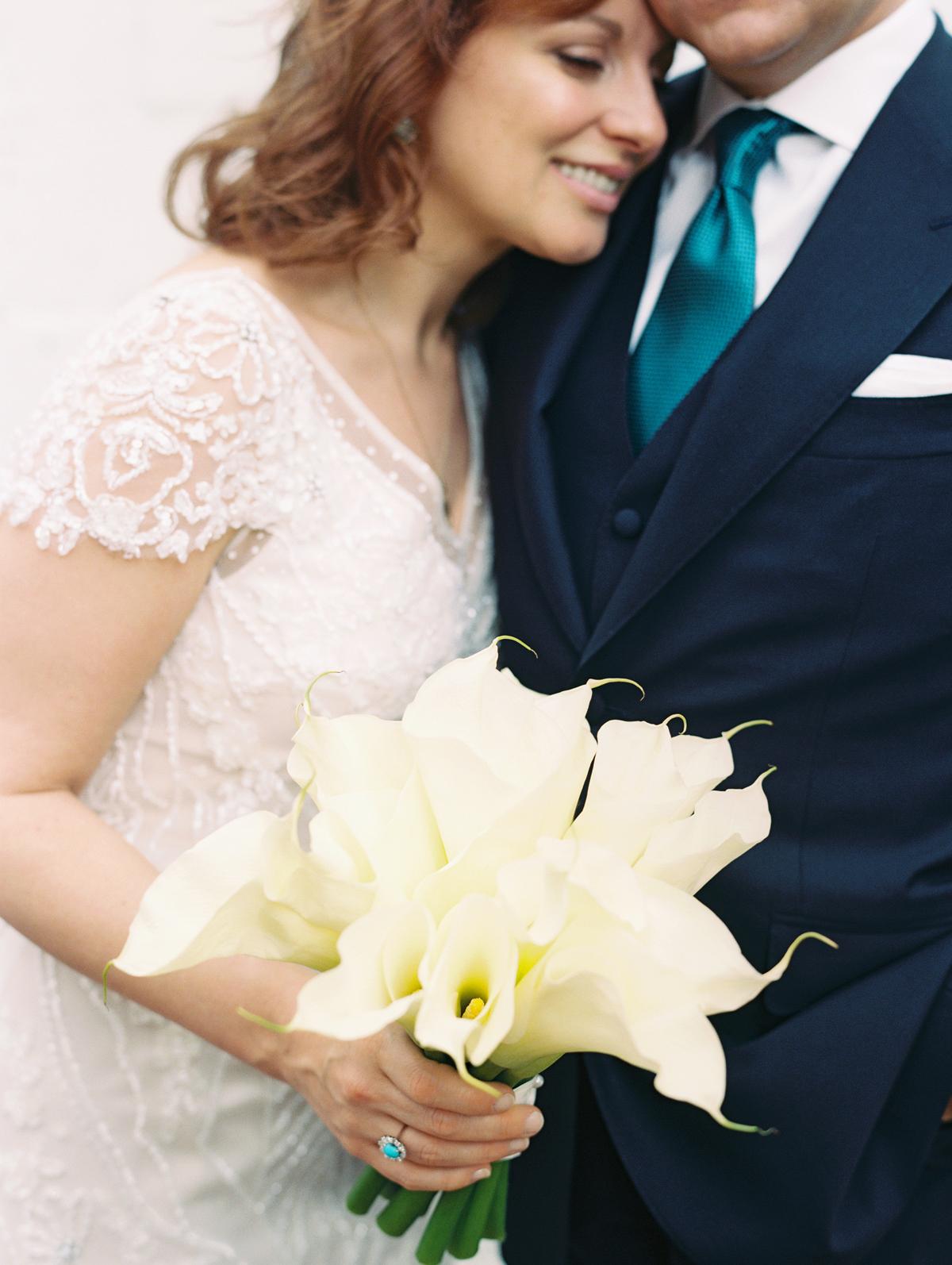 single flower wedding bouquet calla lilies held by bride embracing groom