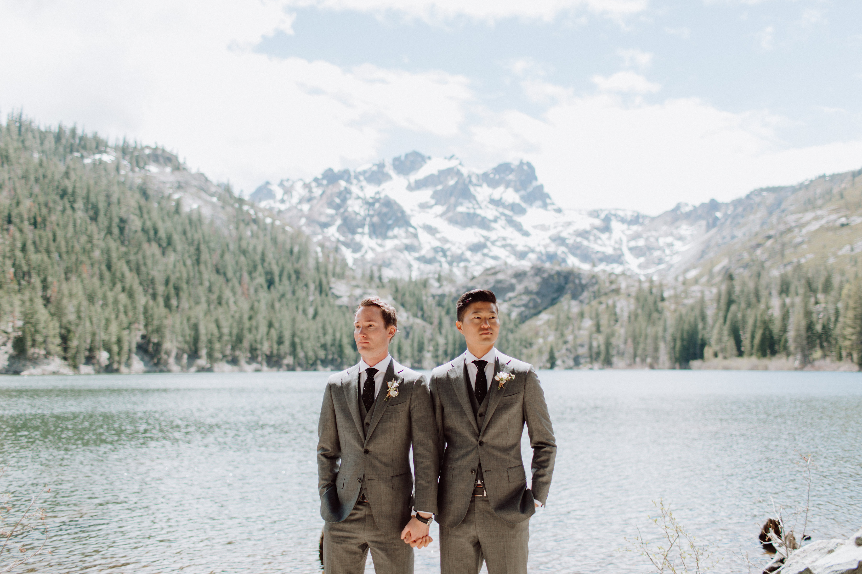 grooms holding hands in front of lake and mountains