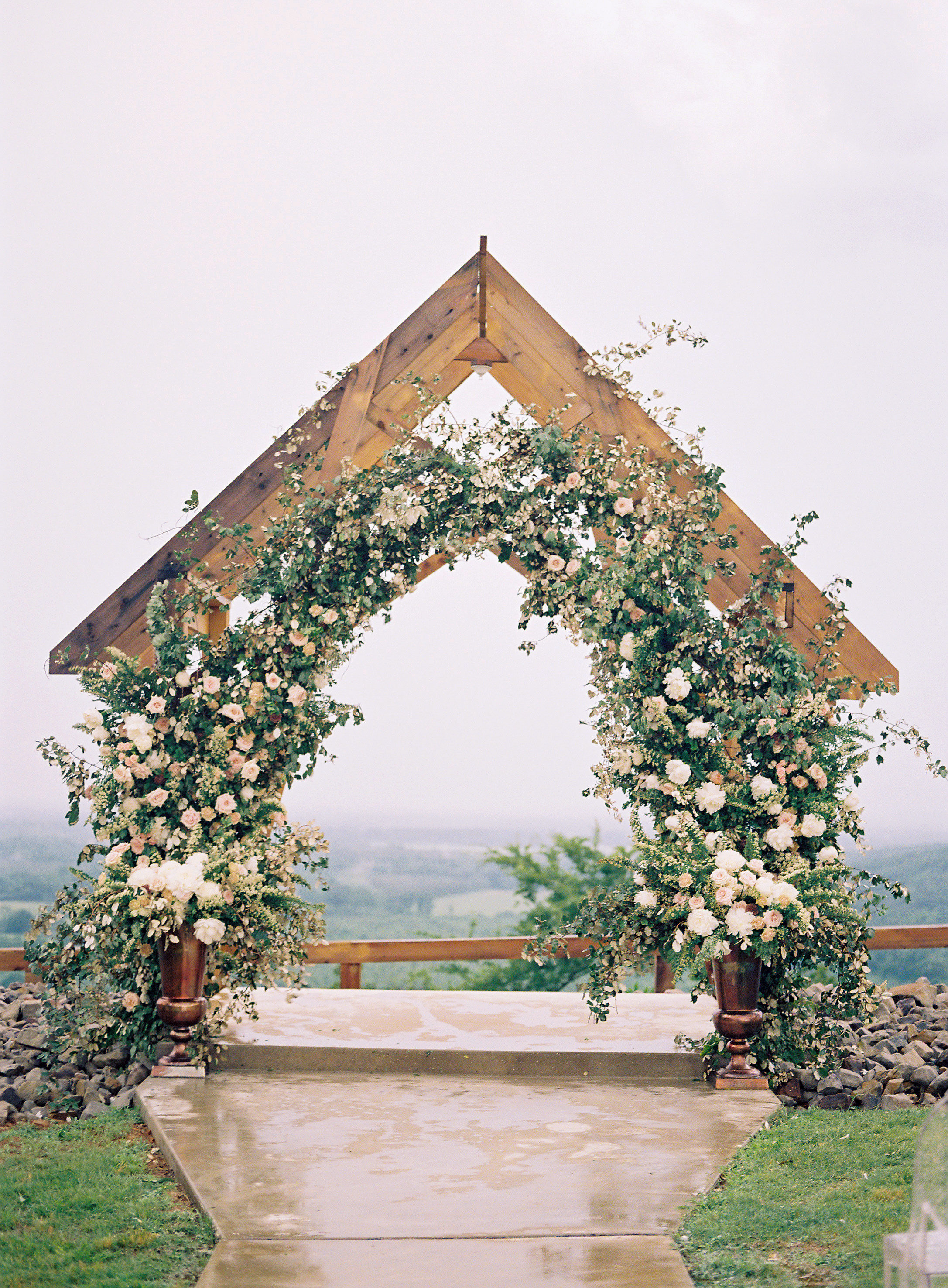 wedding archway with greenery and floral river valley view