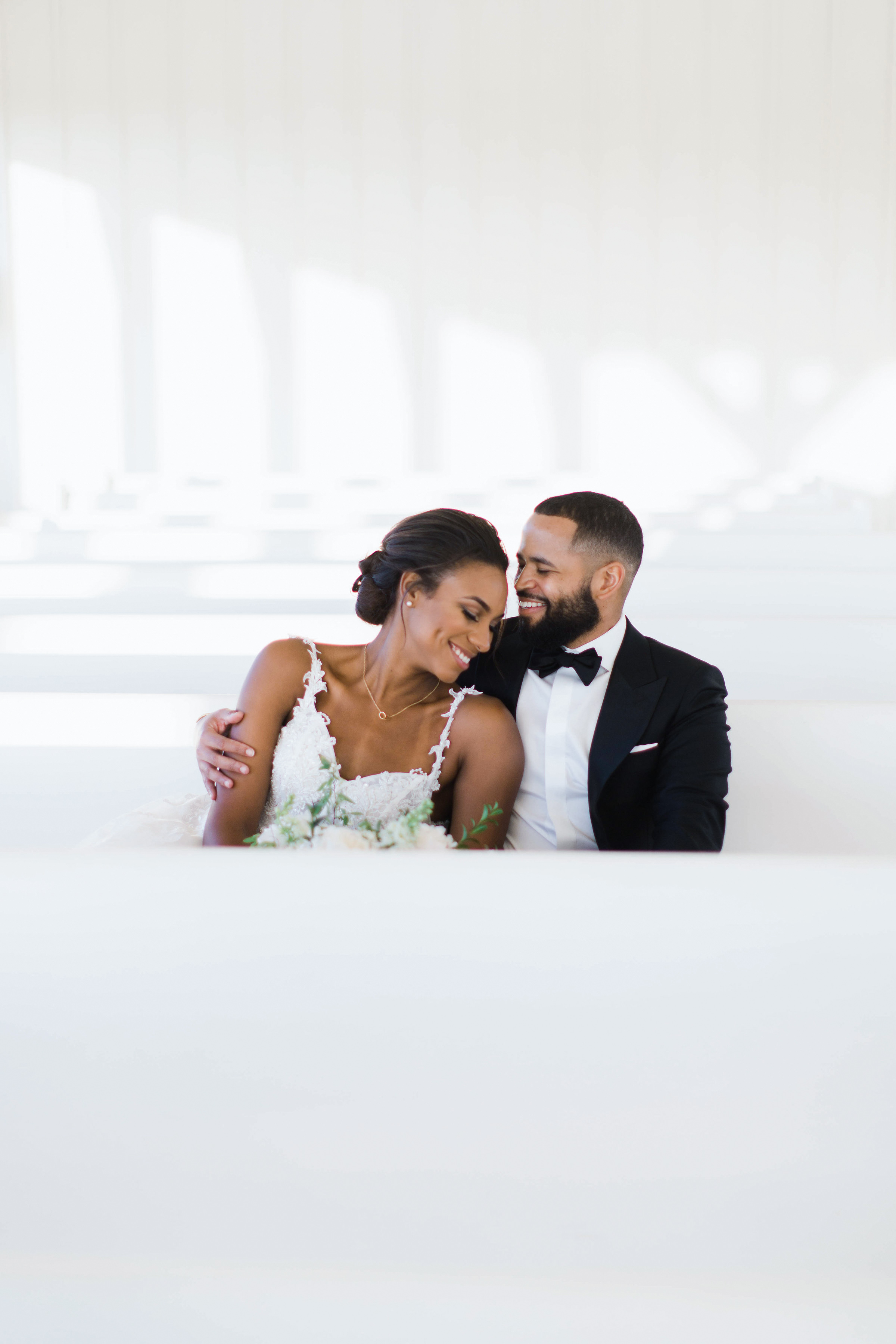 groom happily holding bride sitting in pew