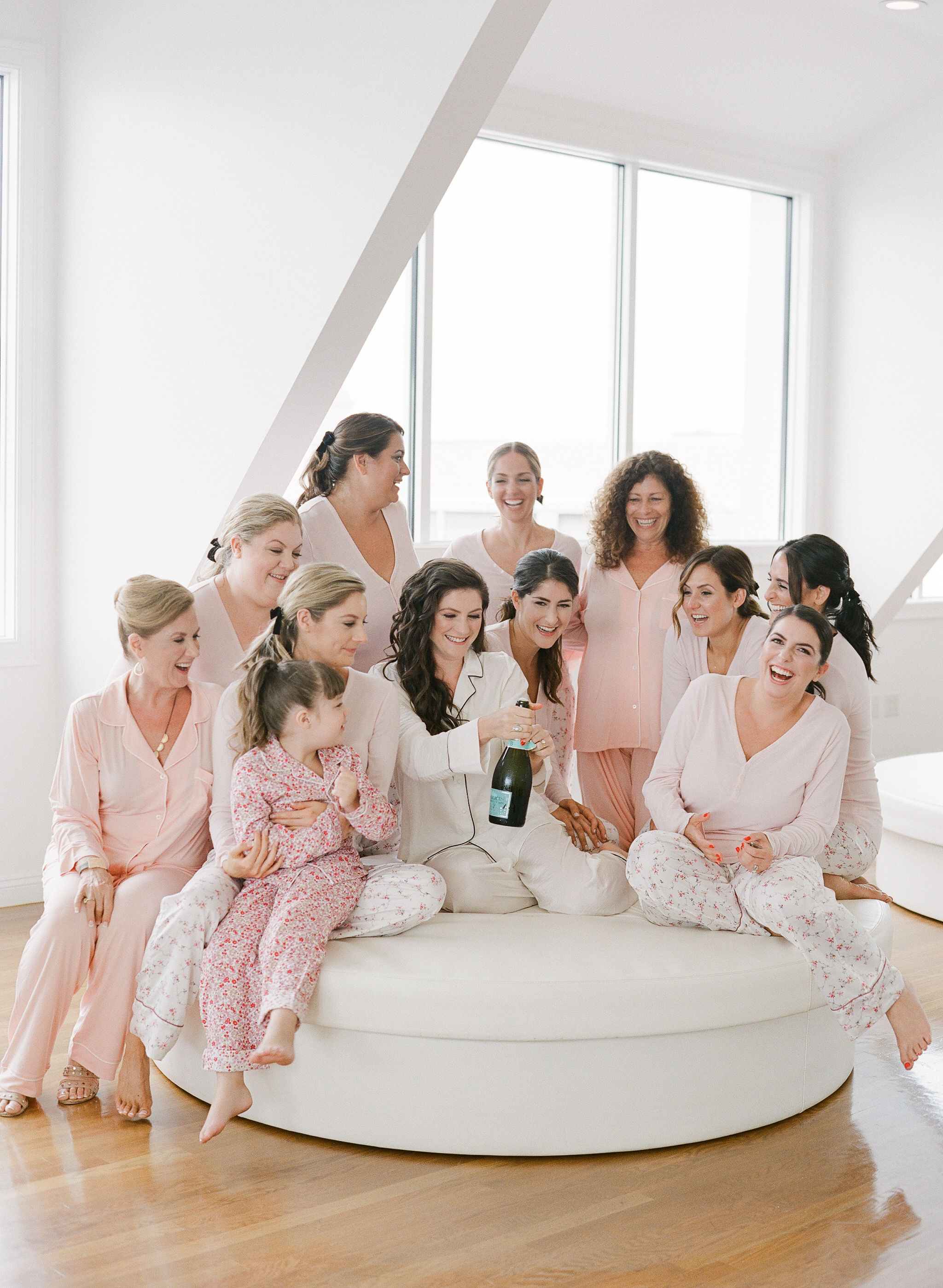 colleen stephen newport wedding bride and bridesmaids in pajamas popping champaign