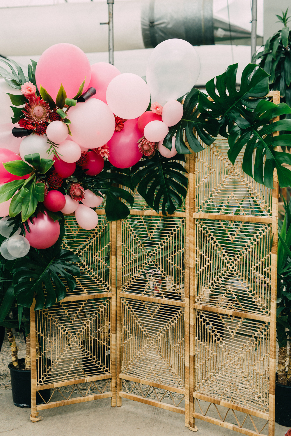 woven rattan wedding decor room divider decorated with pink balloons and palm leaves