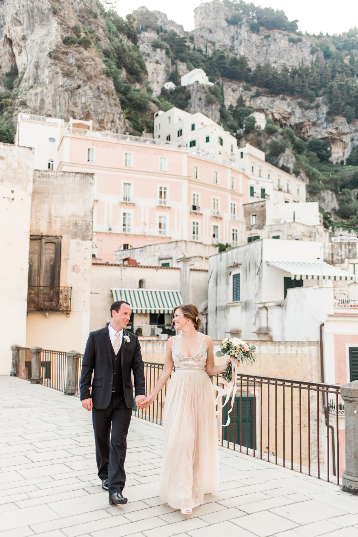 elopement outfit inspiration couple holding hands outside of italian villa