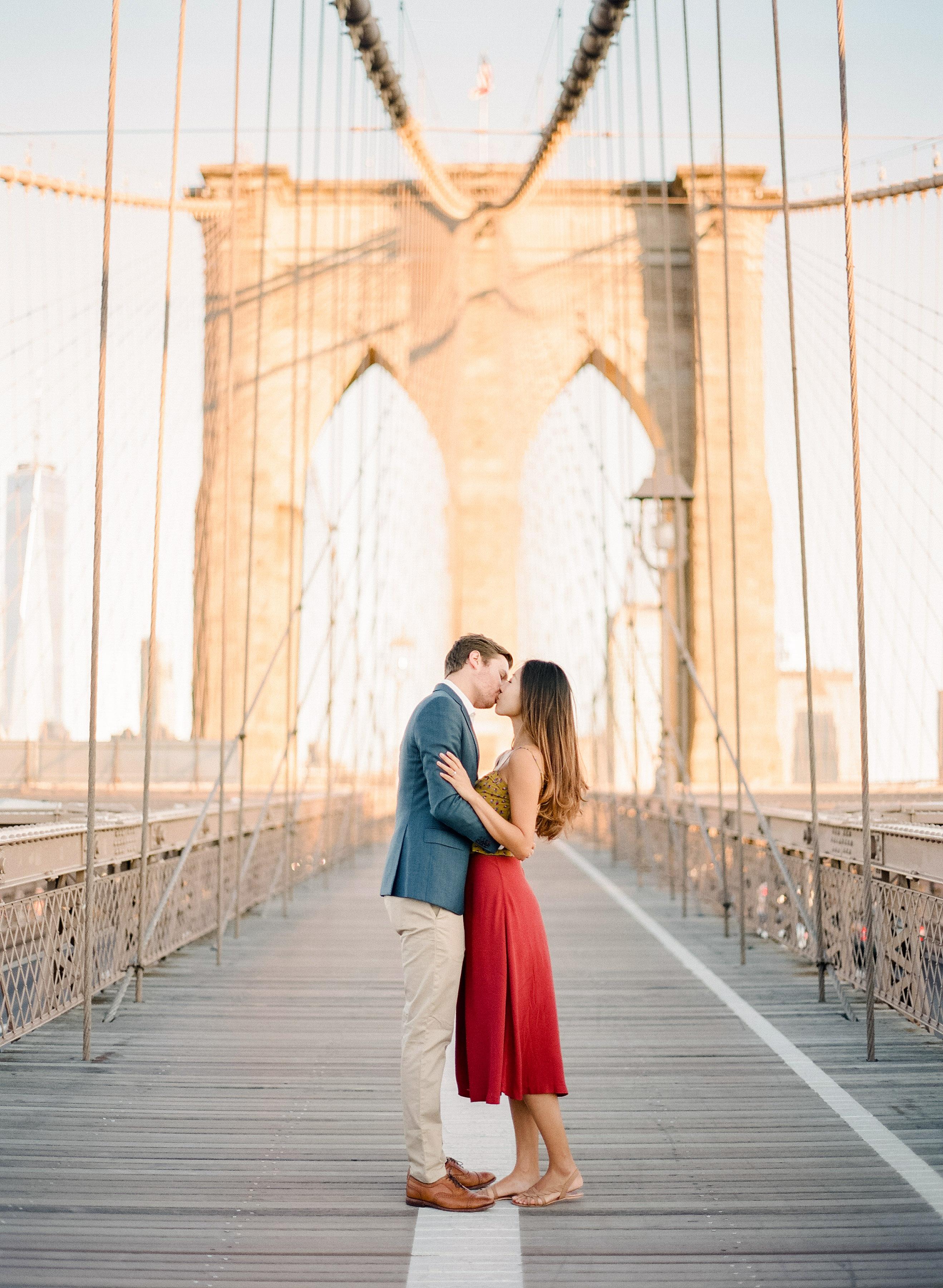 destination engagement couple kiss brooklyn bridge sunrise