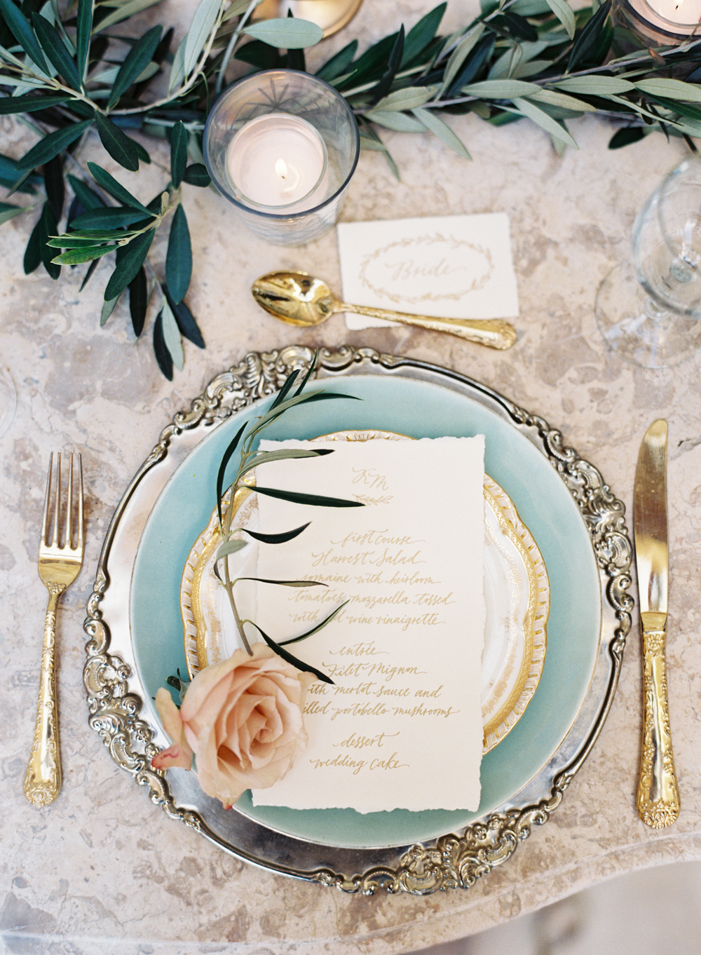 gold and silver place setting with a pink rose atop plate