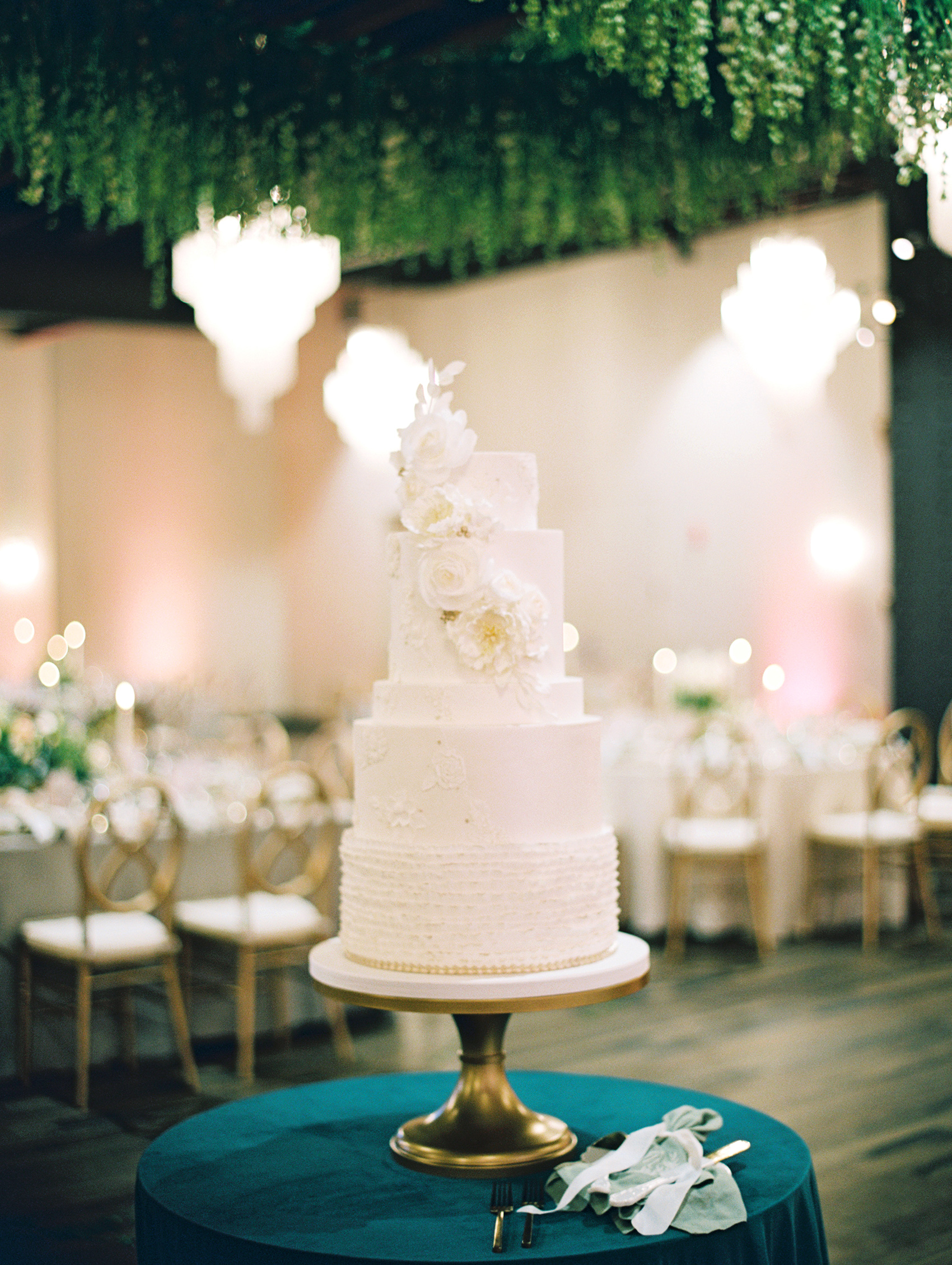 micro tier wedding cakes all white on table with deep teal cloth