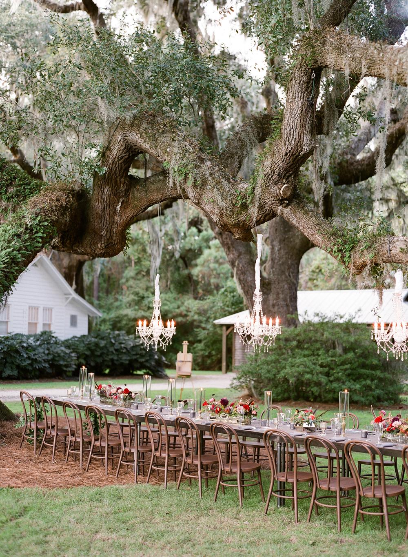 long outdoor dinner table below chandeliers hanging from tree