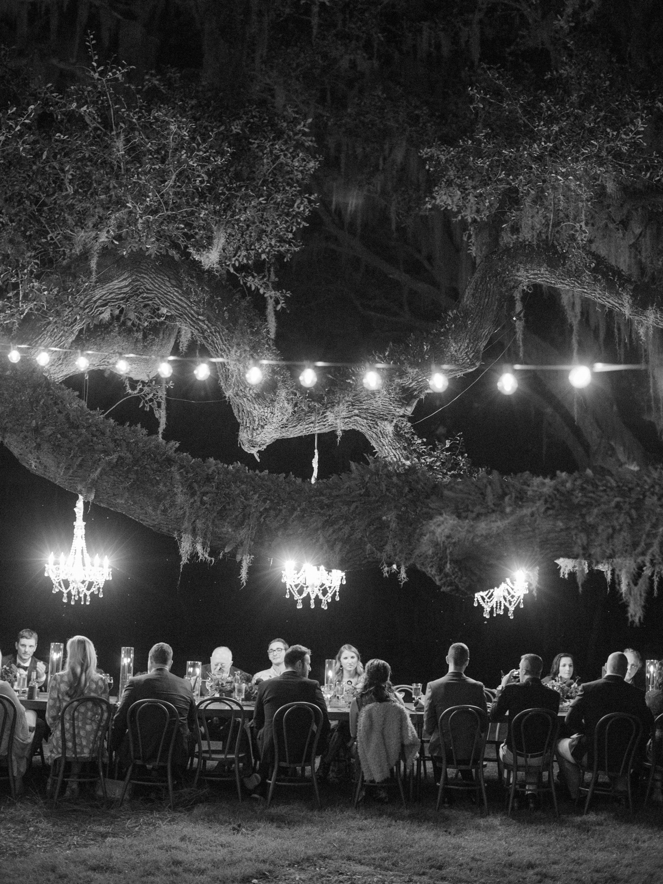 people sit at long table outdoors under string lights and chandeliers