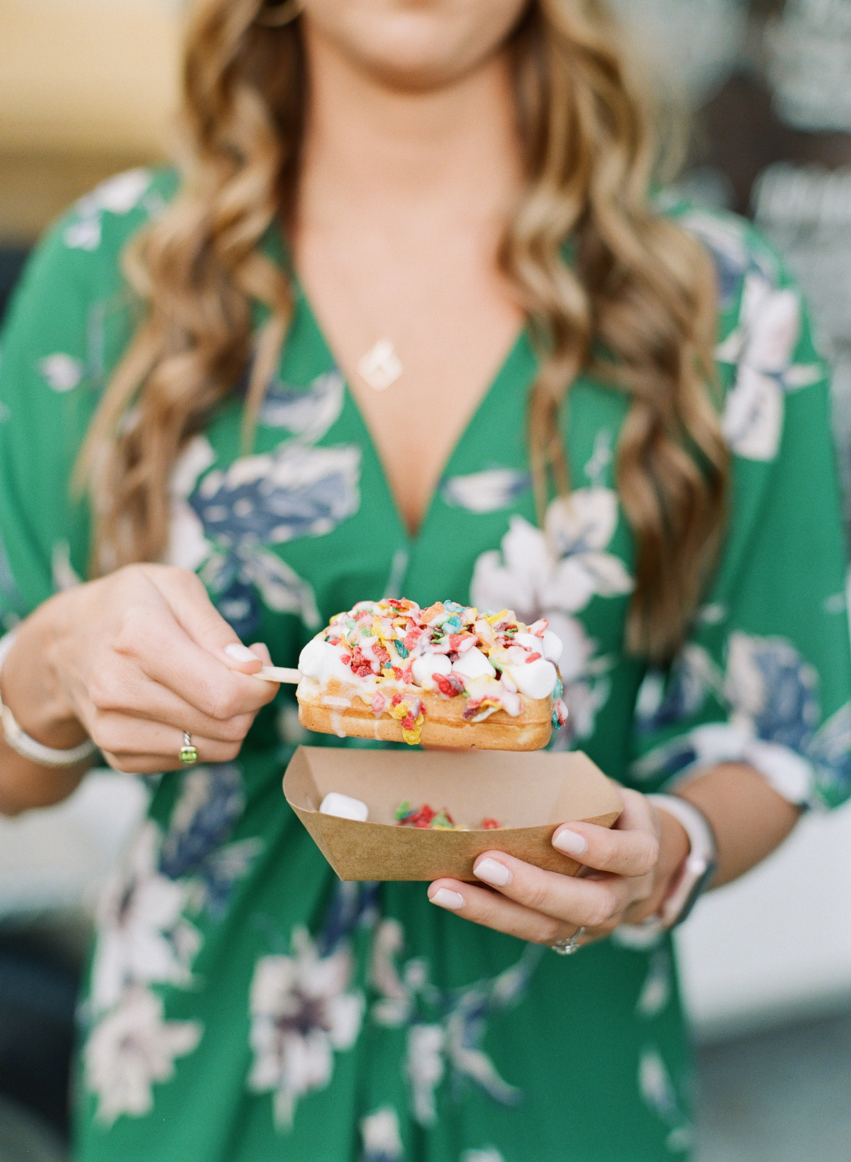 woman holds waffle pop covered in Fruity Pebbles and marshmallow