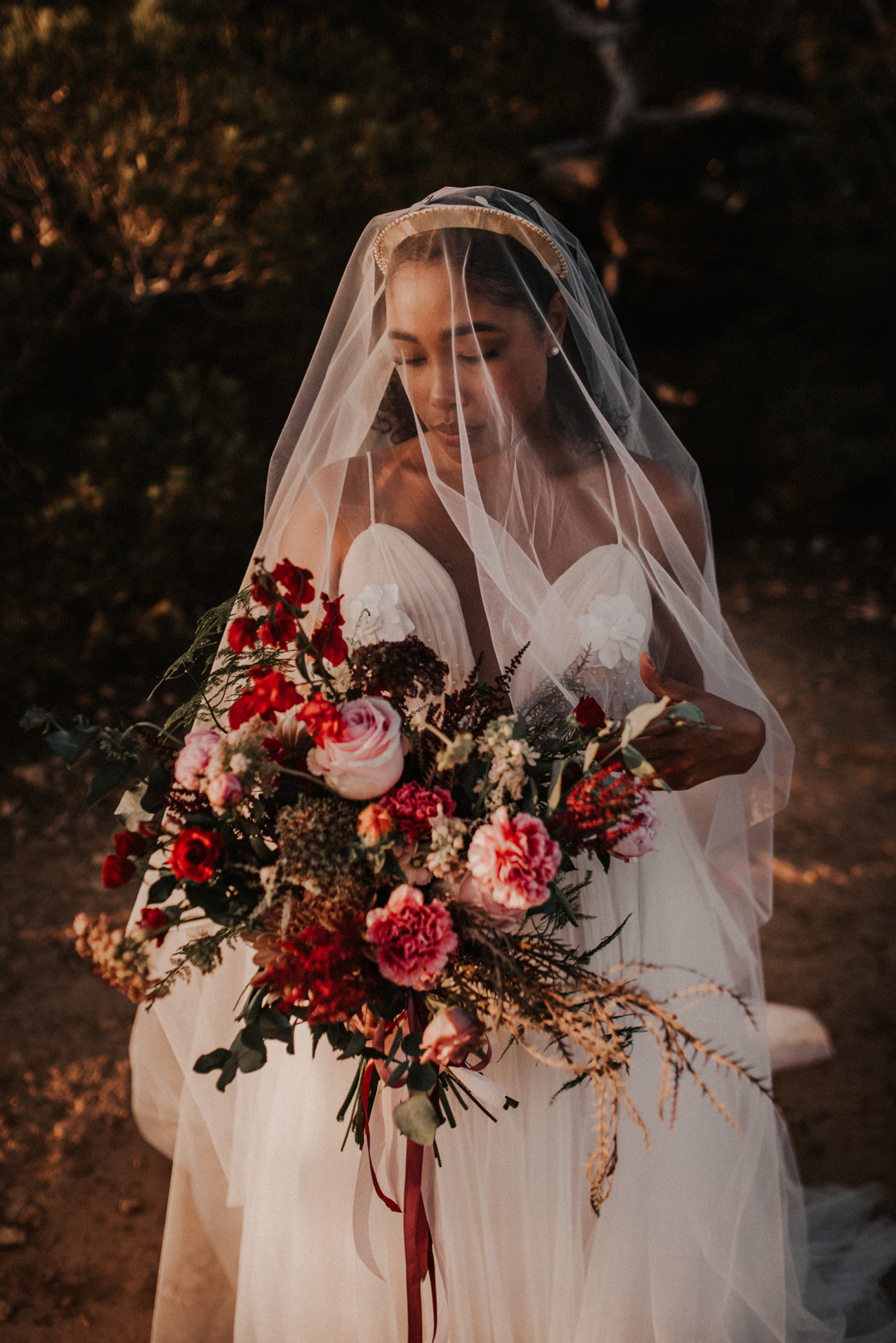 bride holding bouquet of pink and red blooms