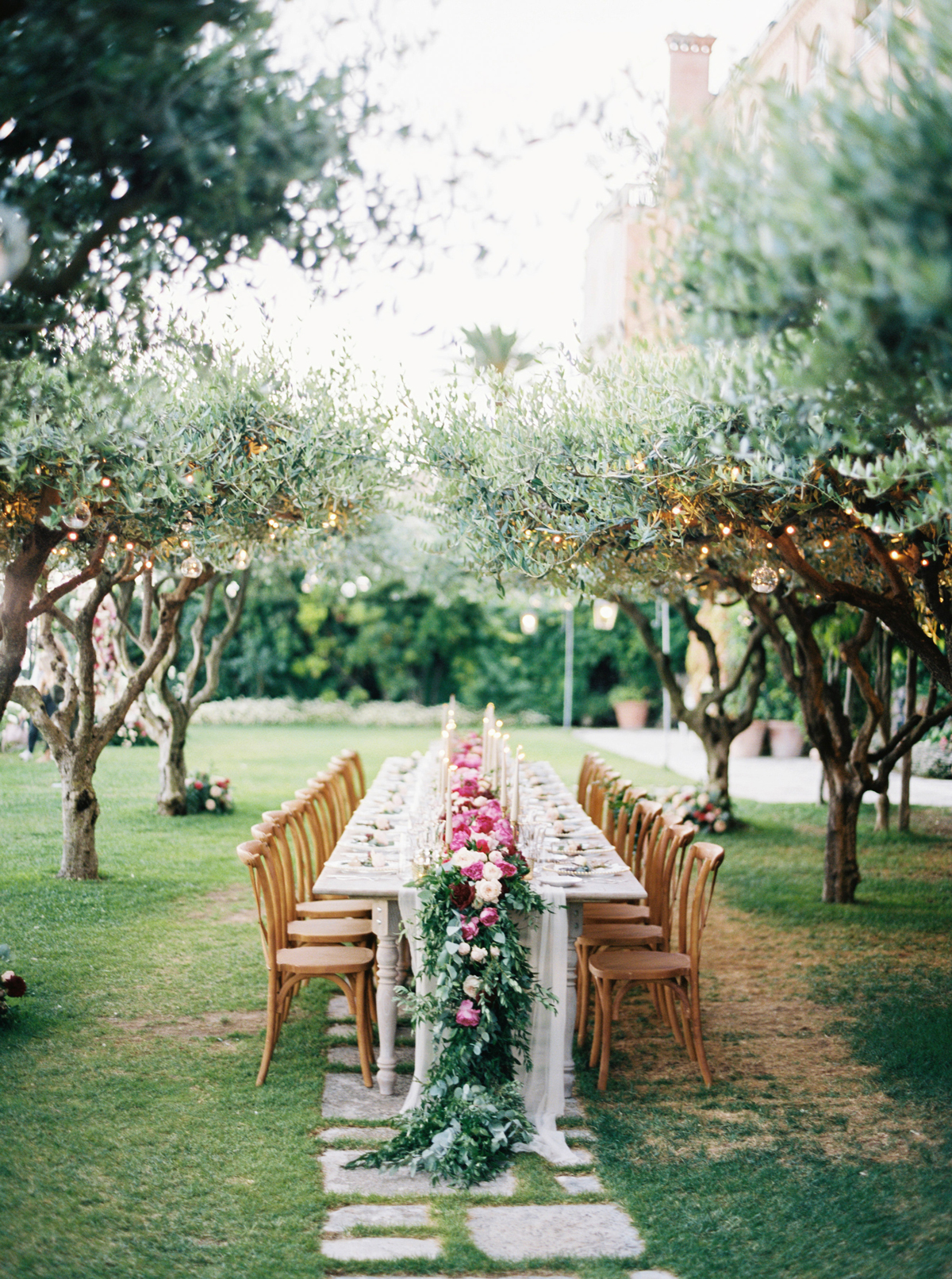 allie and joe italy wedding long reception table beneath olive trees