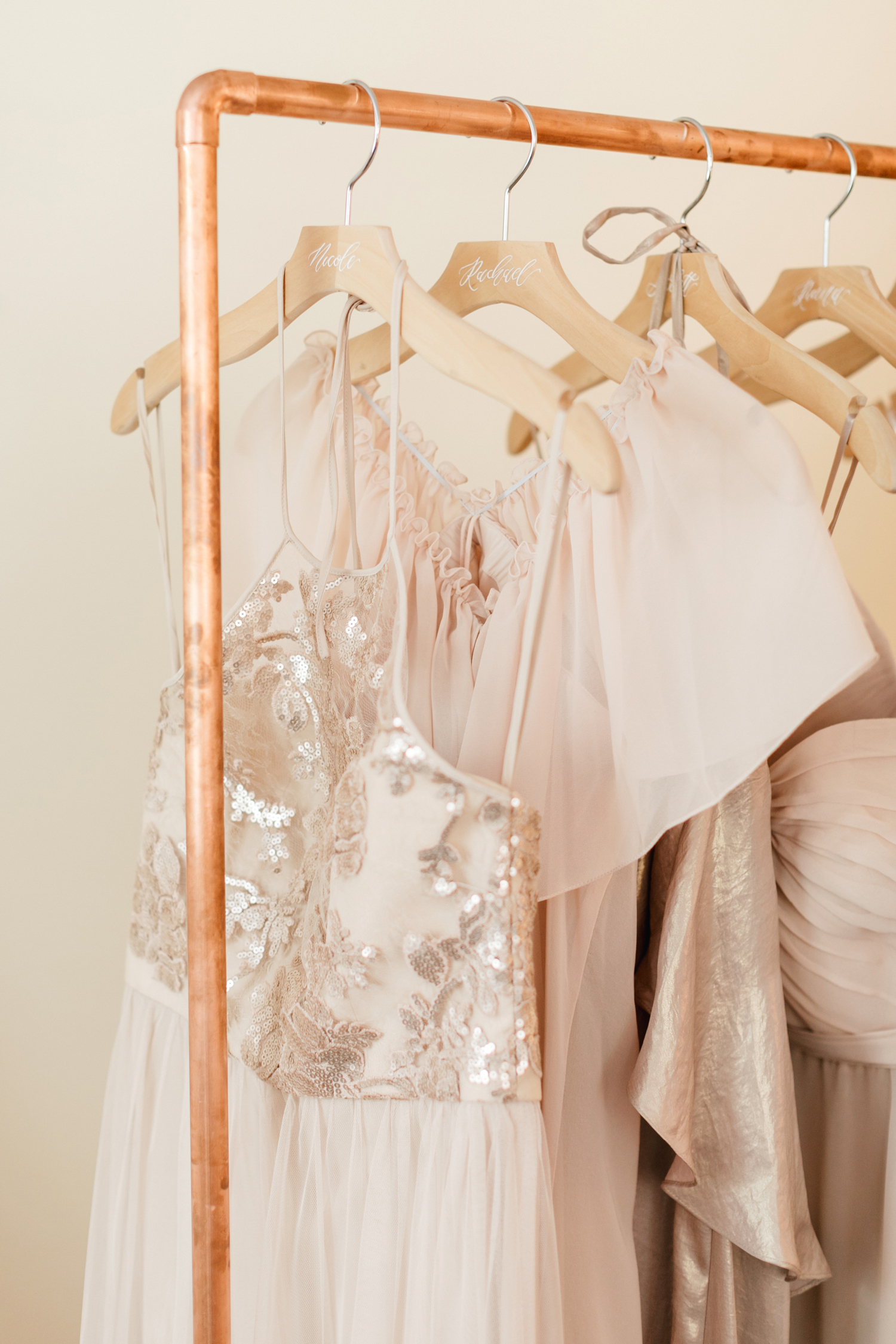 pale blush bridesmaids dresses hanging from copper clothing rack