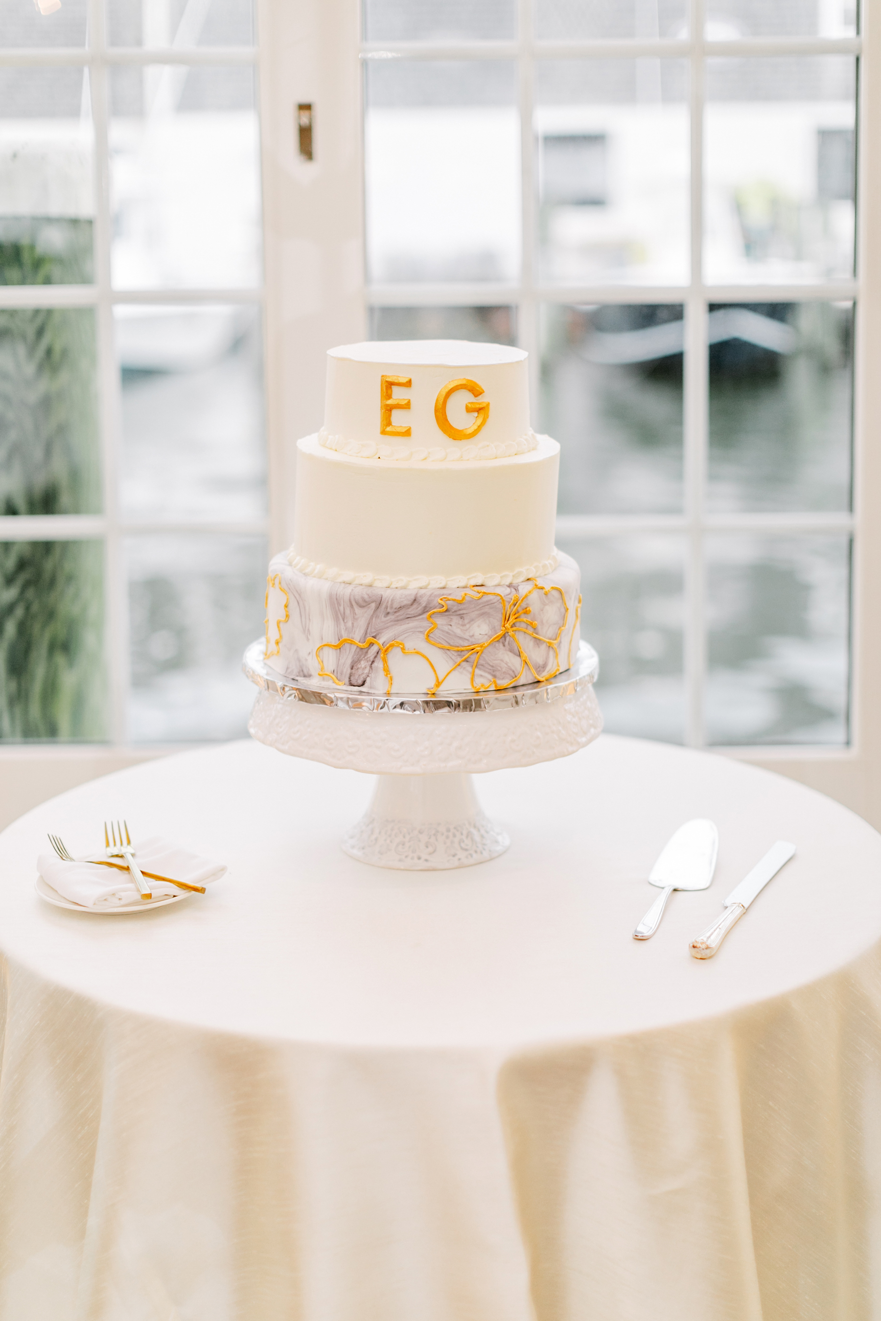 white wedding cake with gold monogram