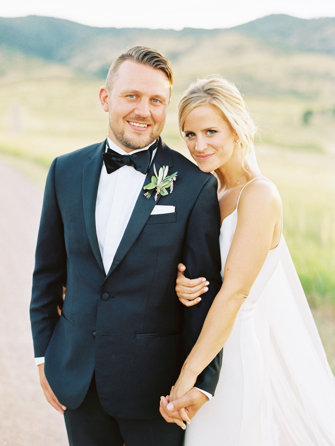 bride and groom stand outside with rocky mountain foothills behind them