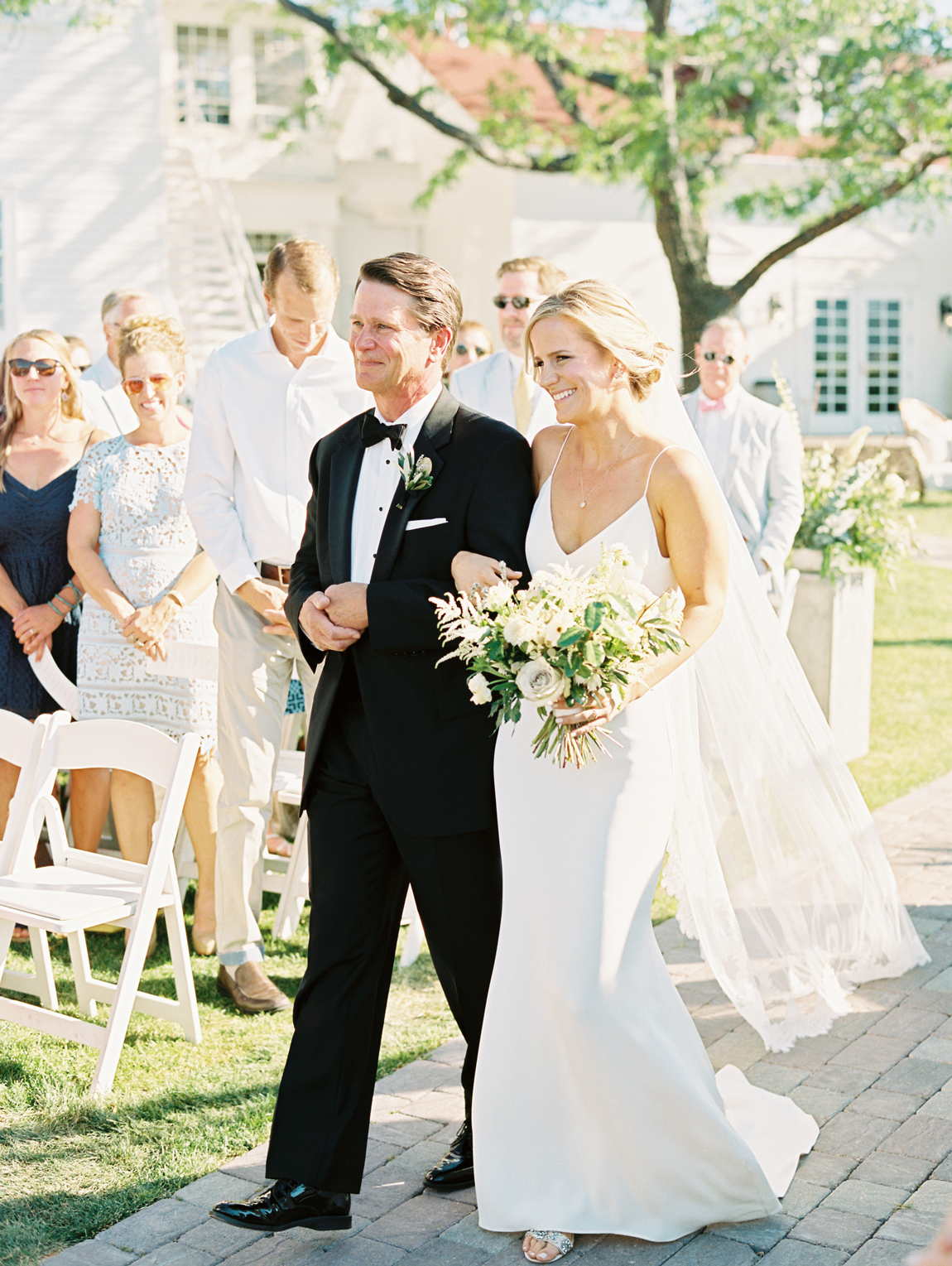 father of the bride walks bride down the processional aisle