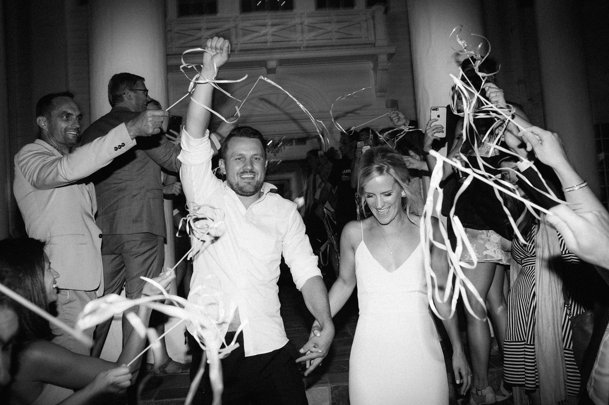 bride and groom surrounded by guests with streamers during sendoff
