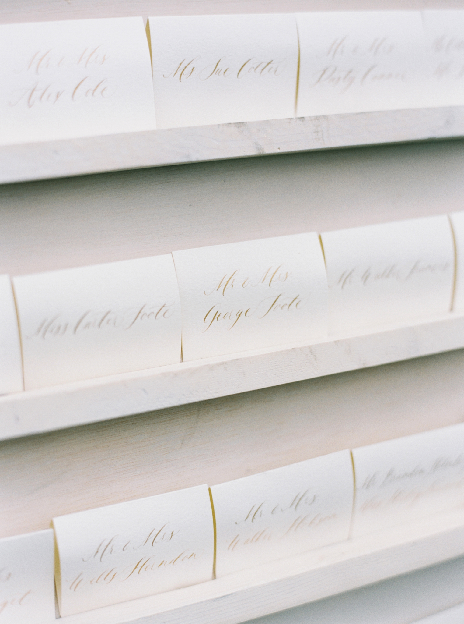 white stationary escort cards with gold calligraphy