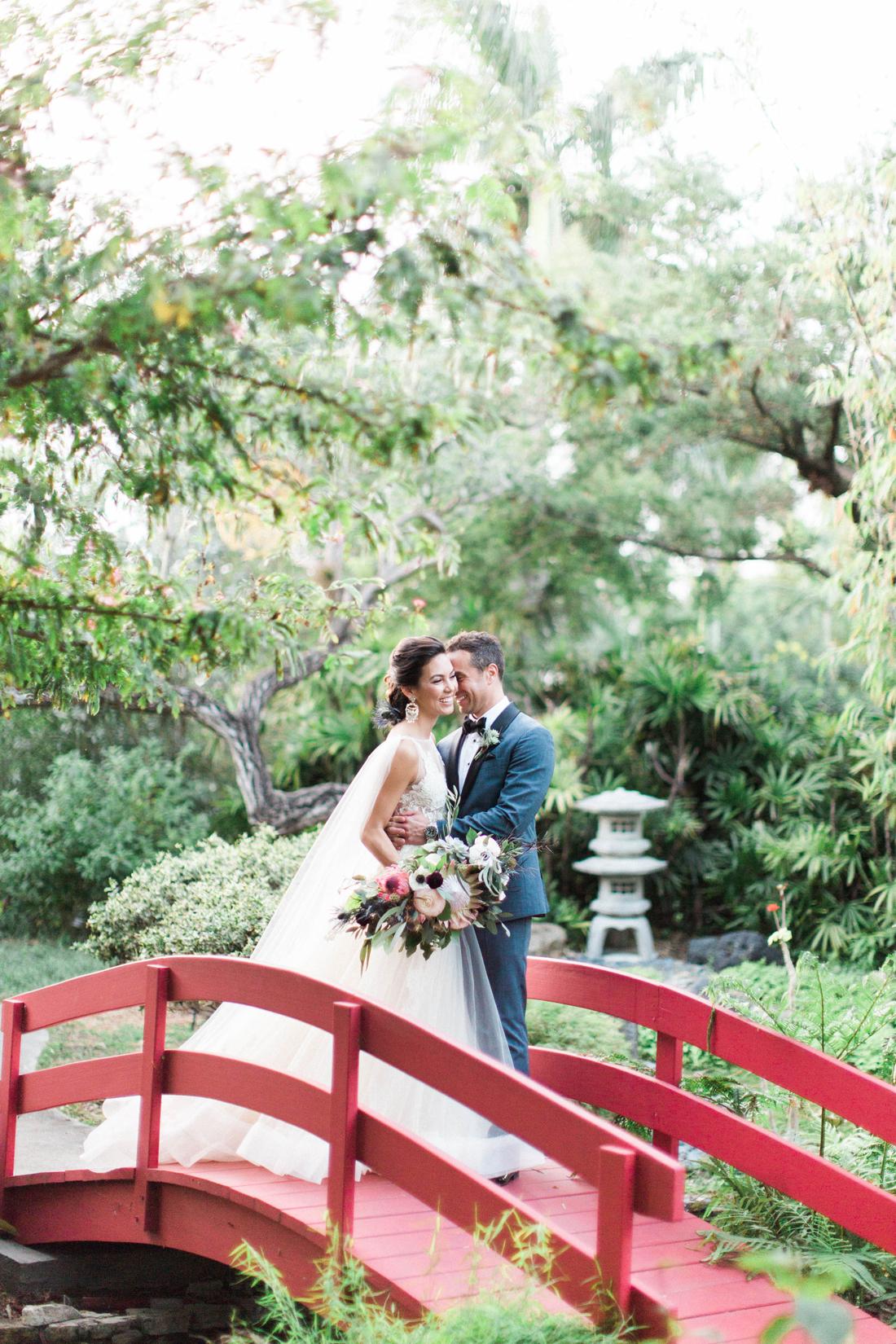 bride and groom pose on red wooden bridge in garden
