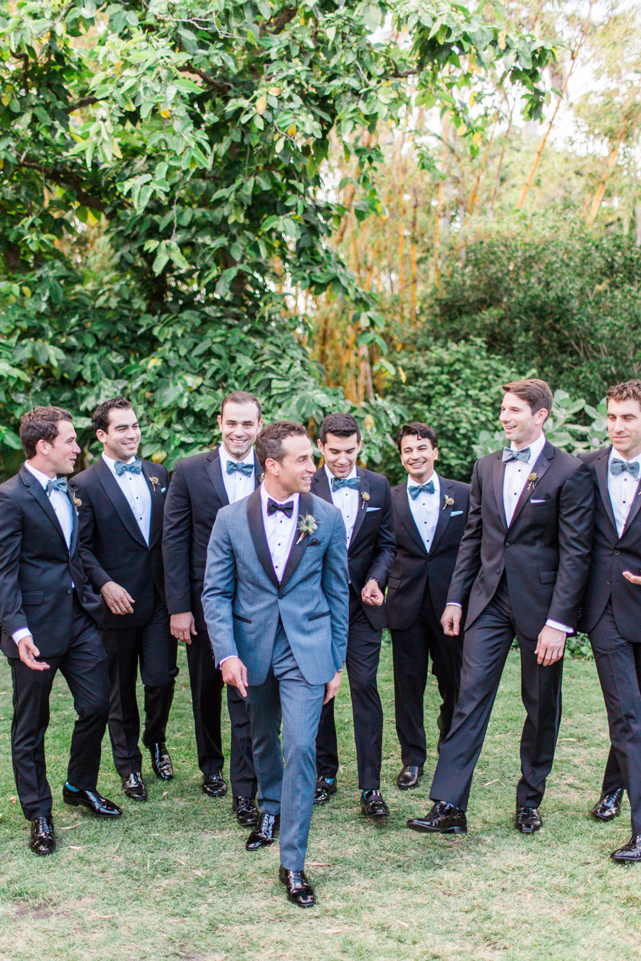 groom poses with groomsmen smiling