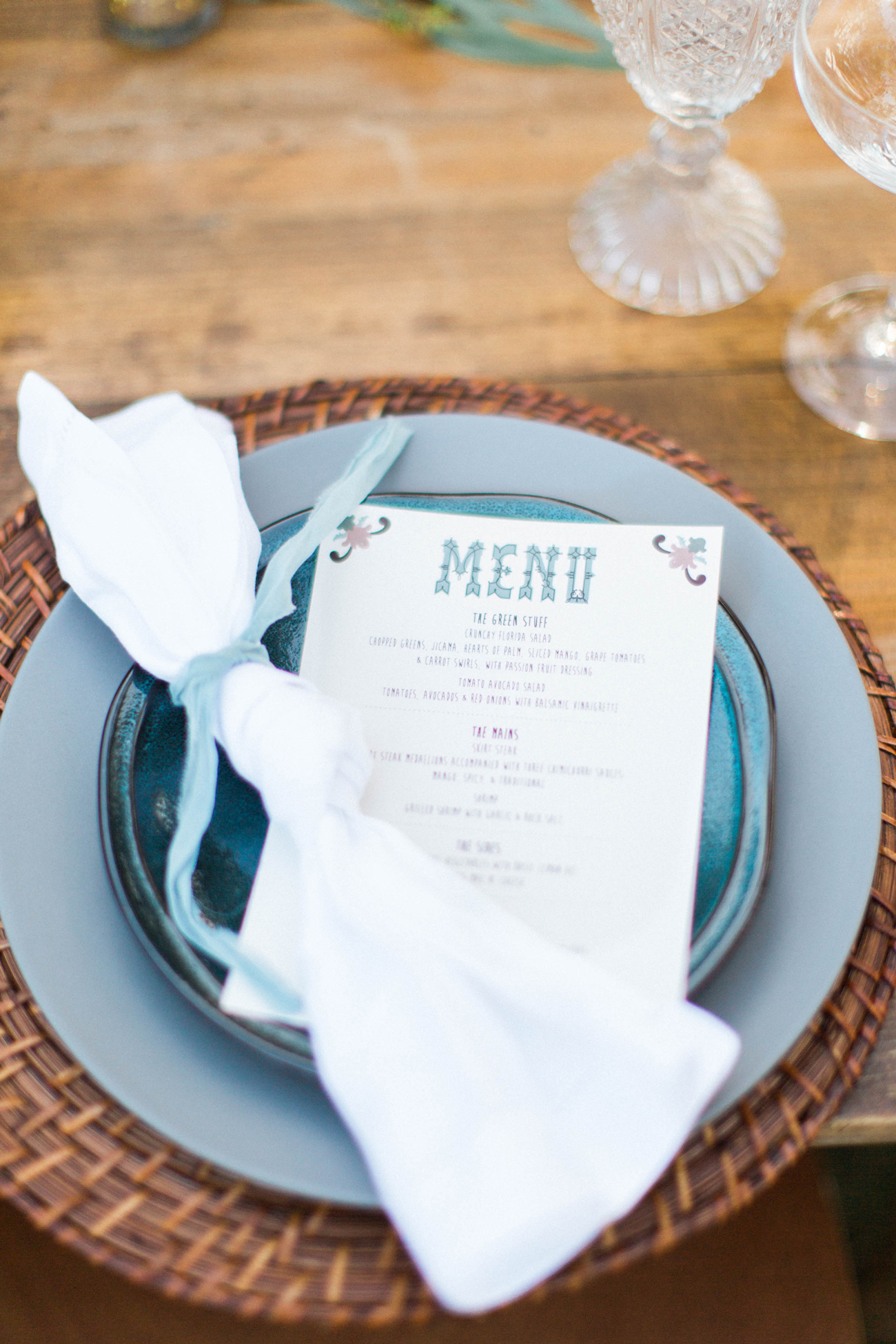 layered blue place setting with white cloth napkin wrapped in ribbon