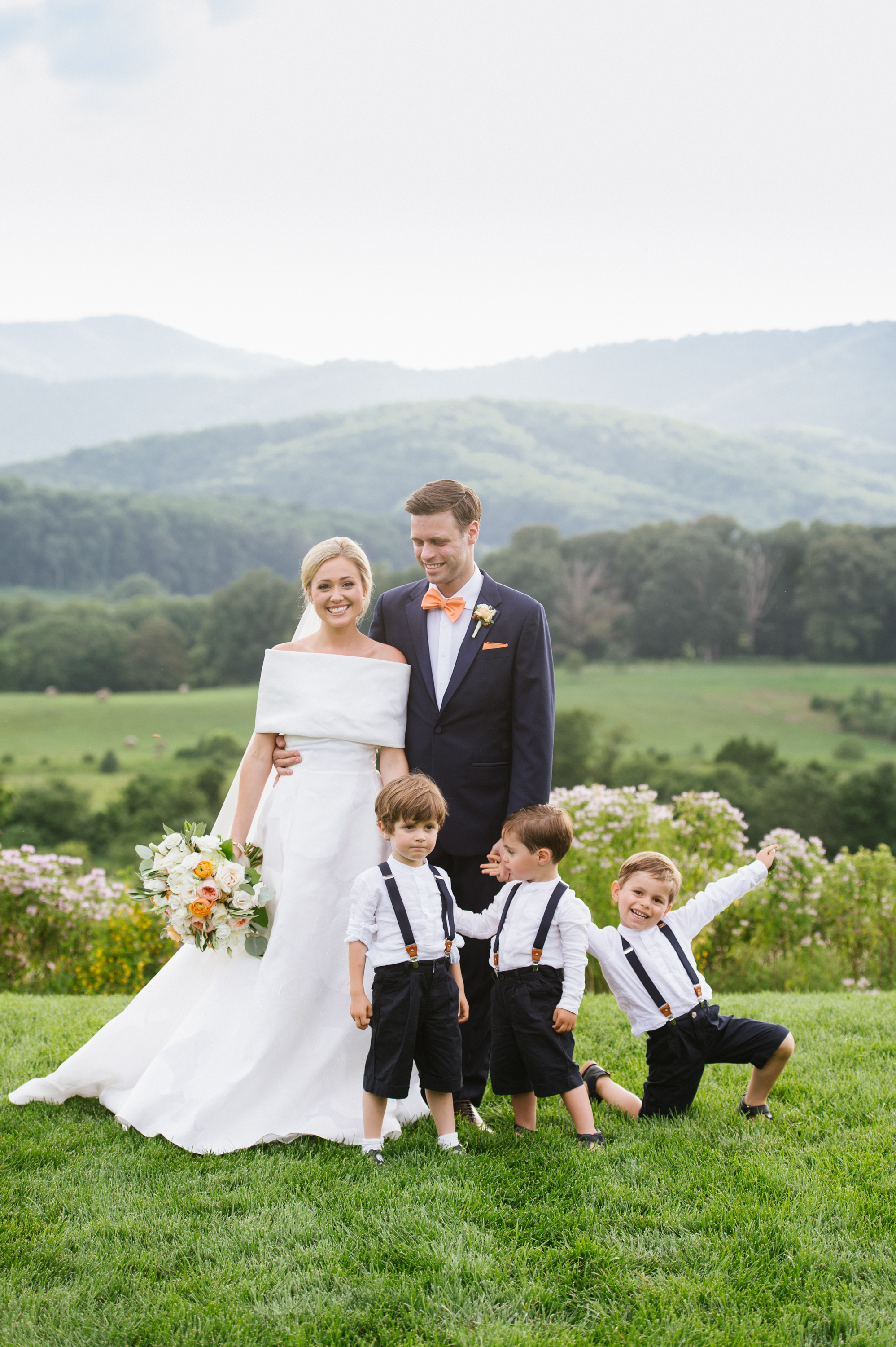 three ring bearers wearing black suspender and white button downs