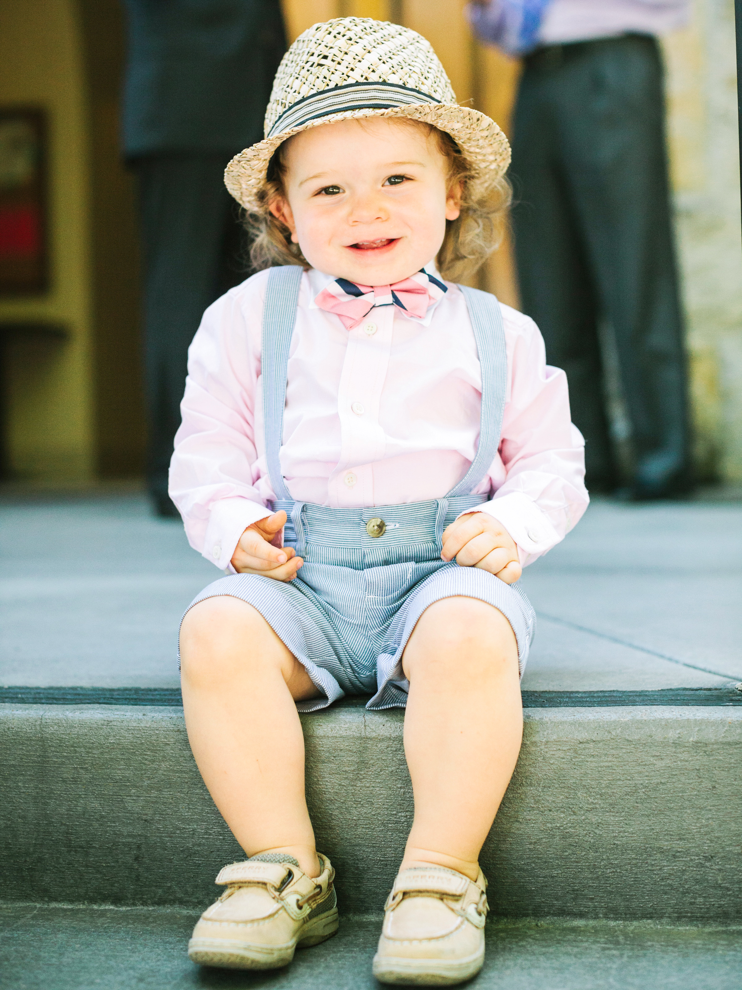 ring bearer wearing pink shirt and suspenders