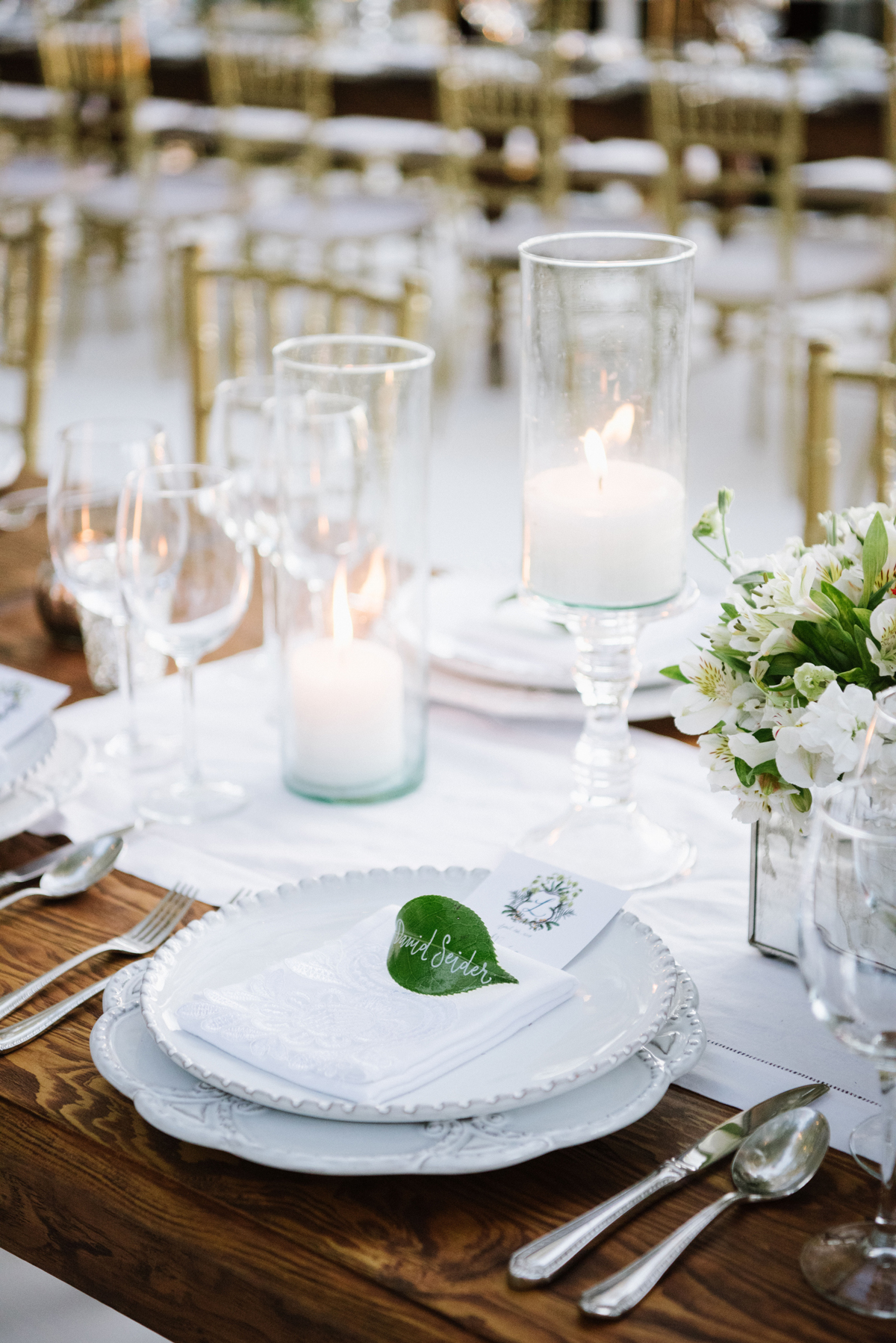 white place setting with leaves as place cards