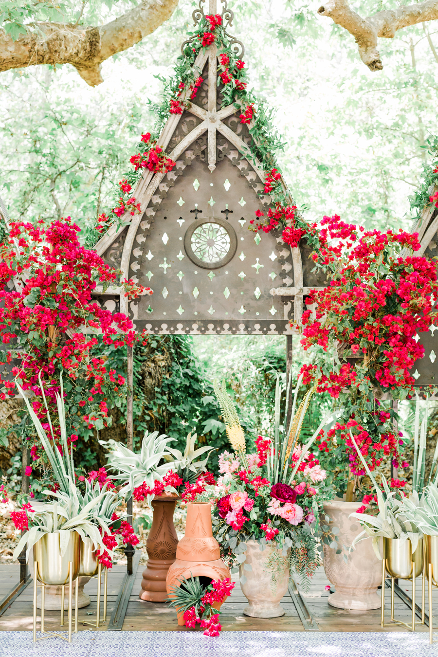 pink and red flowers accent greenery covering cathedral structure