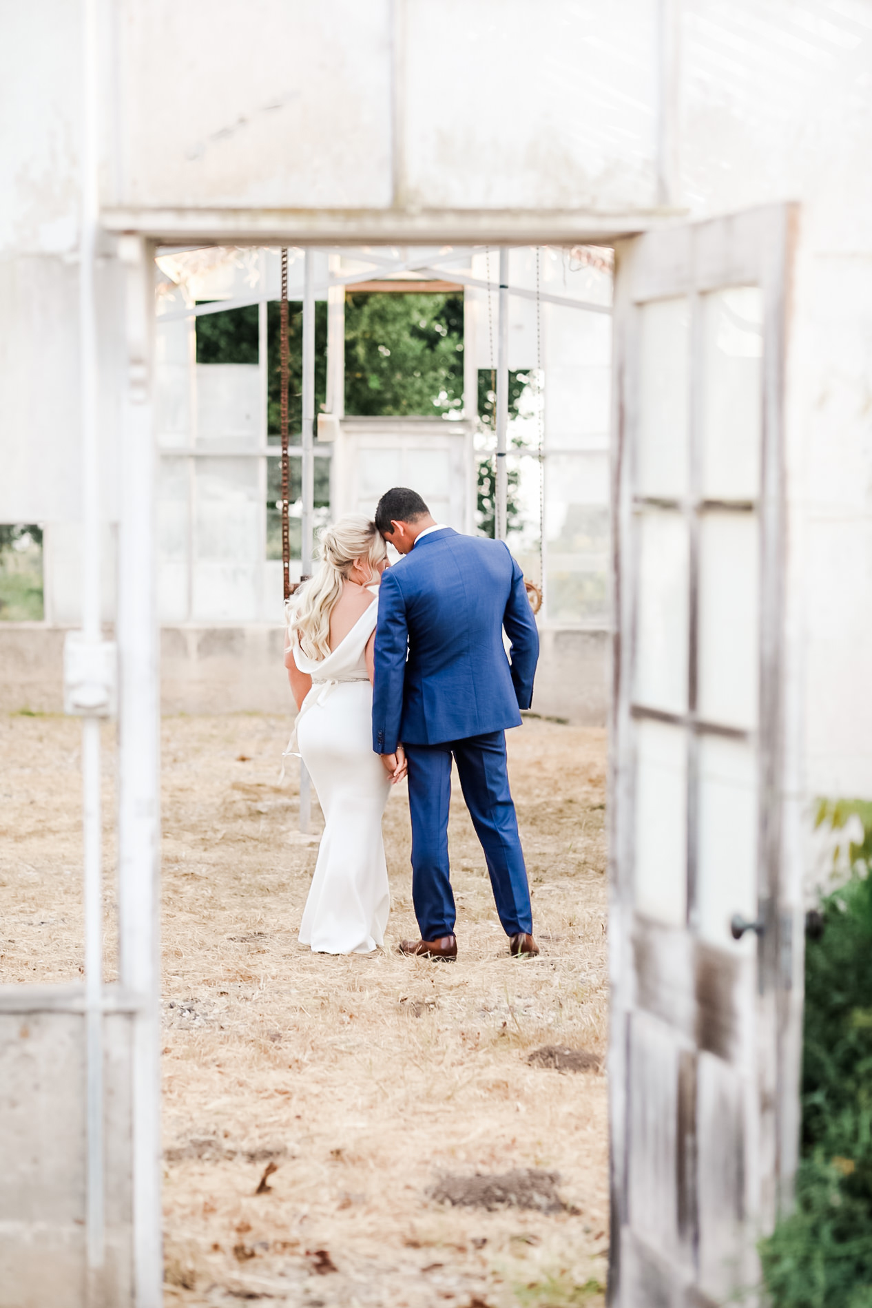 bride and groom pose with backs to camera