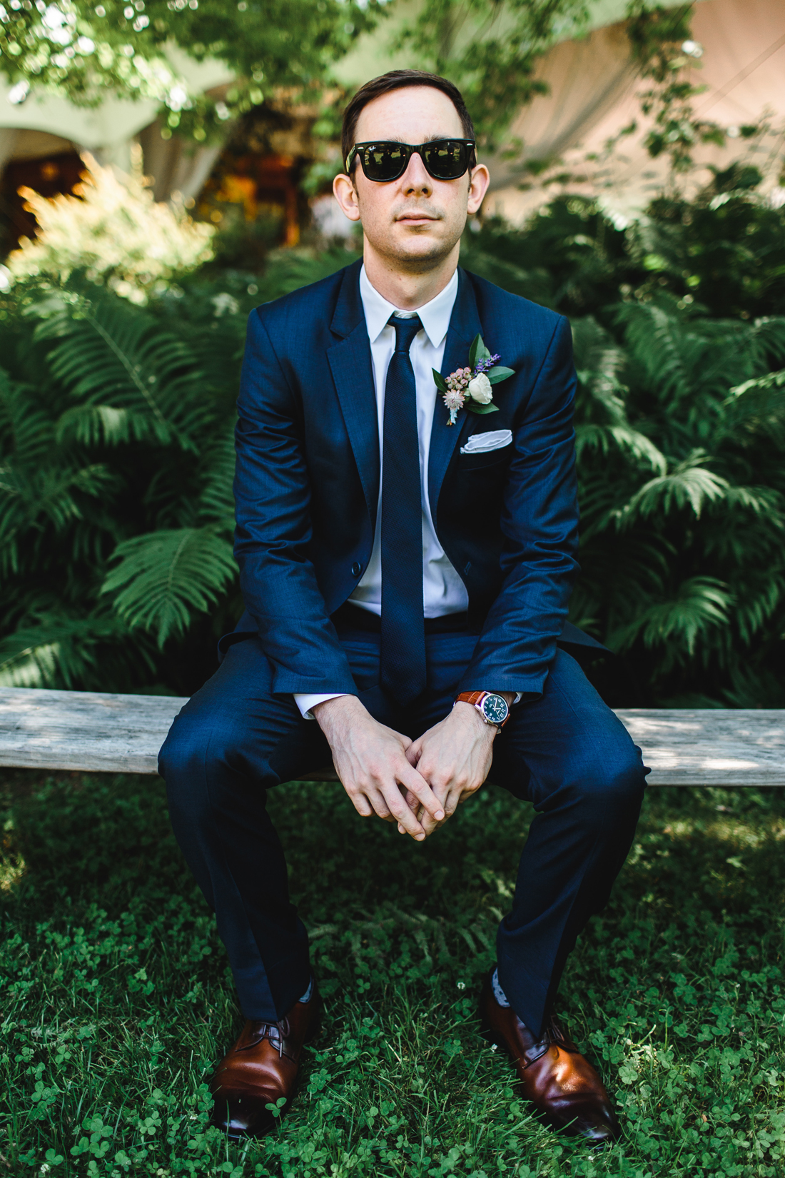 wedding guest wearing sunglasses sitting on outdoor bench