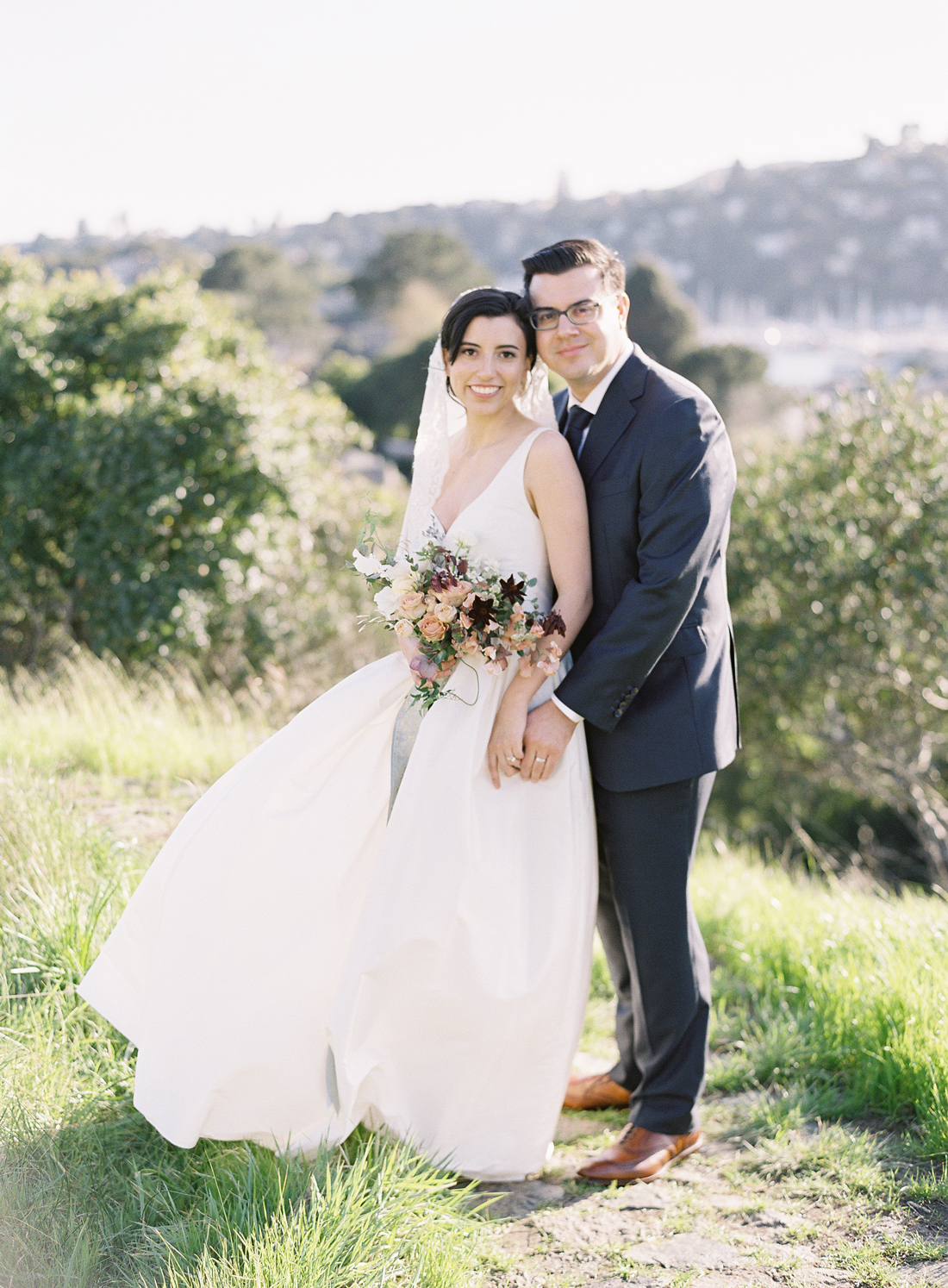 bride and groom pose for wedding photos on green hillside