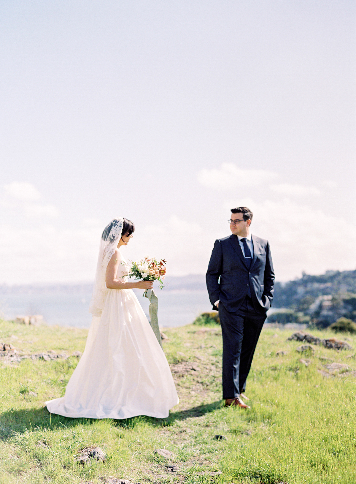 bride and groom share first look on green hillside