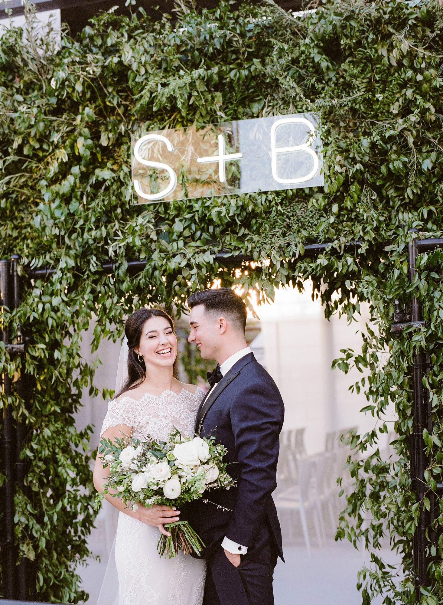bride groom laughing under initials neon sign
