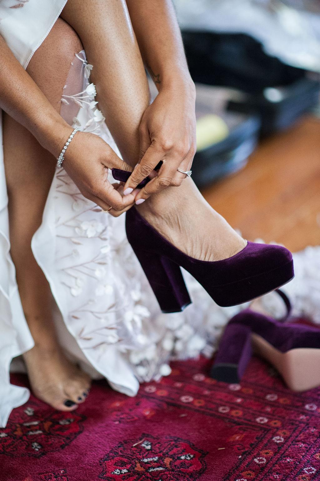 bride putting on aubergine velvet pumps