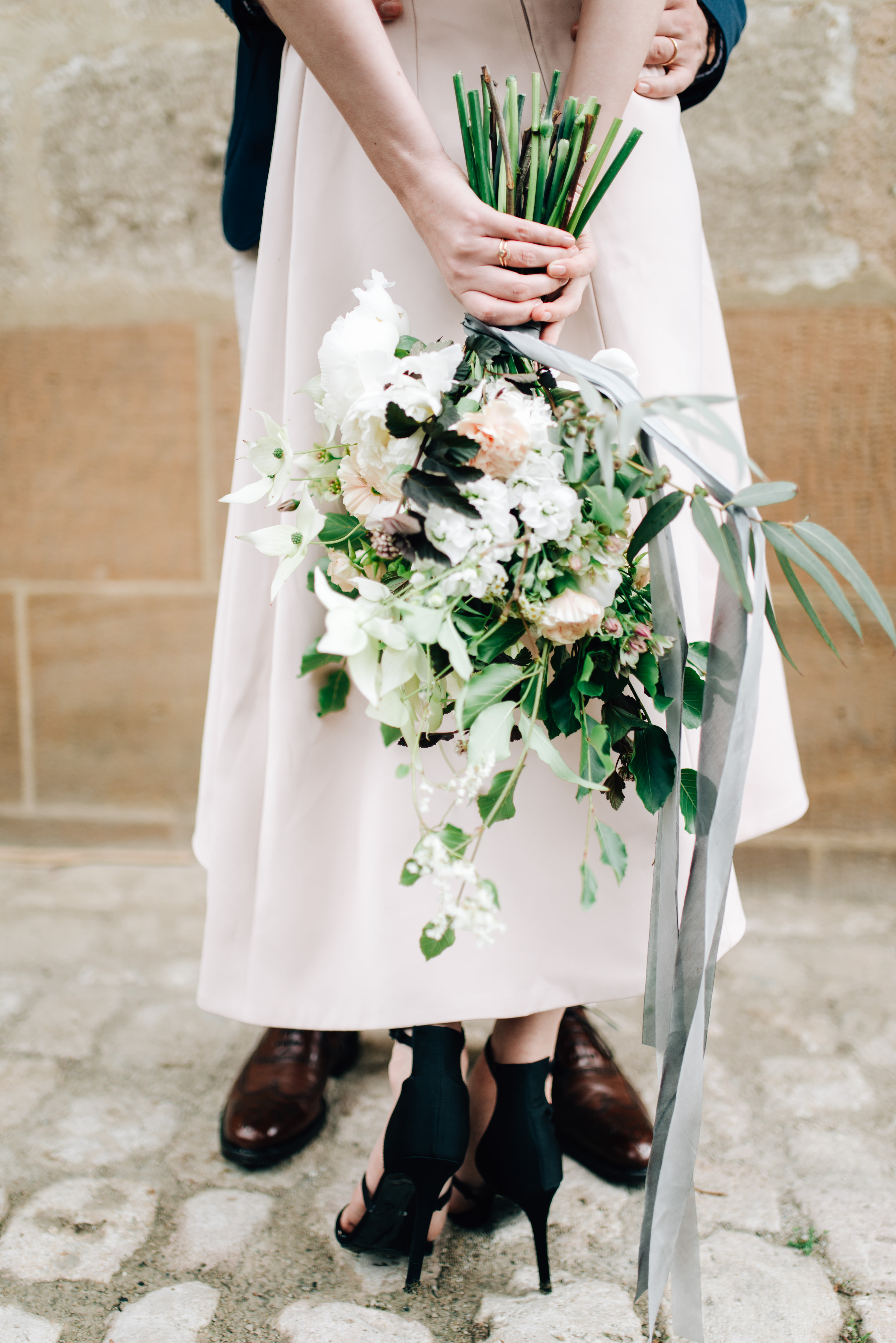 bride holding long-stemmed bouquet behind her back