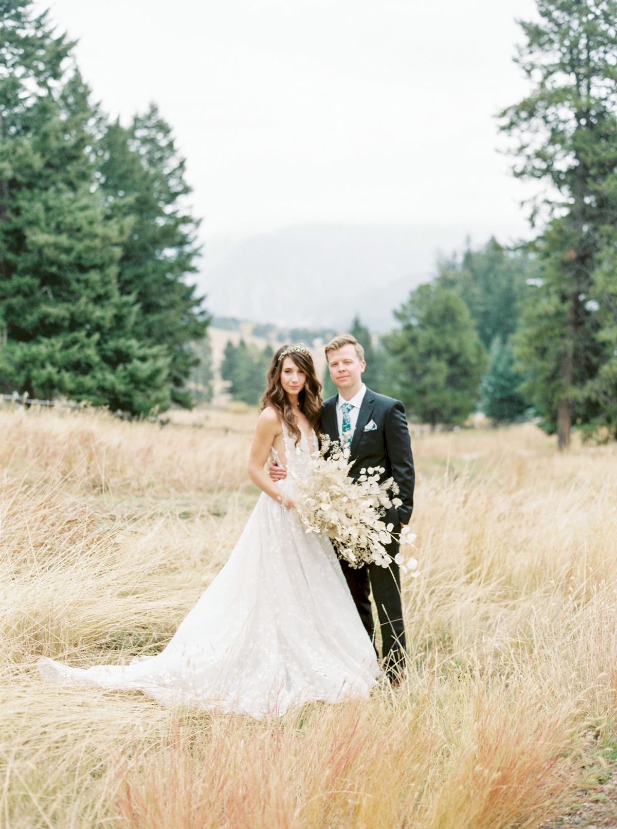 bride and groom in field with pine trees in background