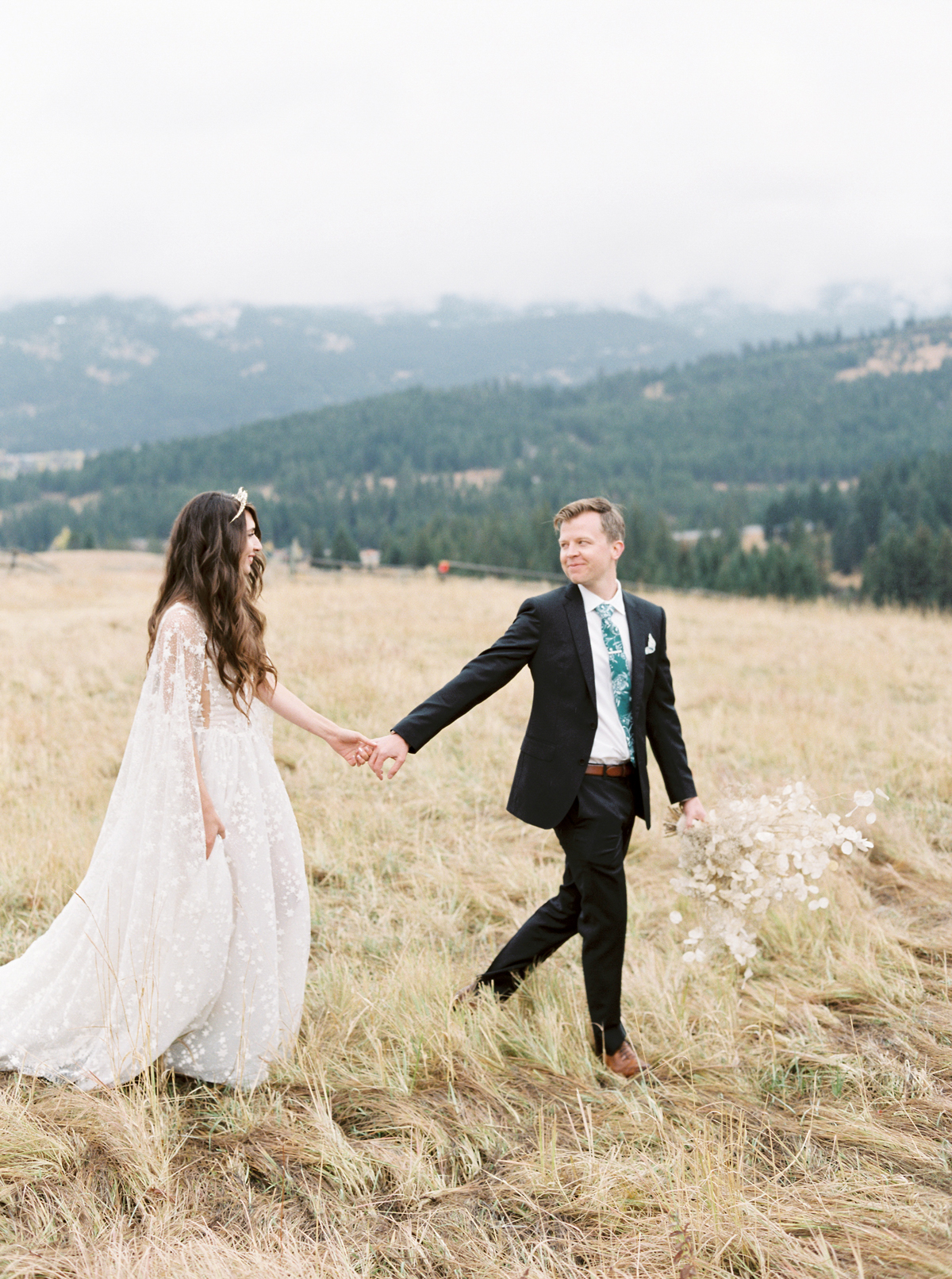 bride and groom holding hands on mountain top